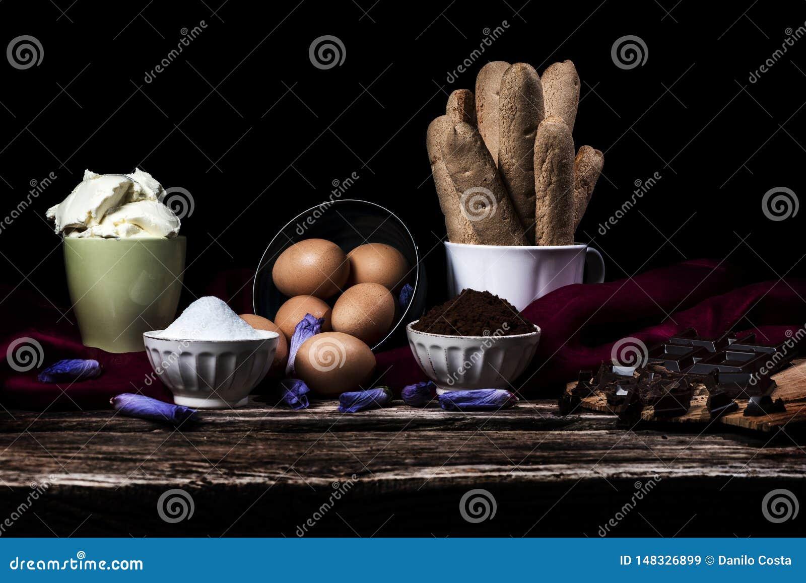 Ingredientes para o tiramisu, o chocolate, o café e o mascarpone italianos em um fundo preto