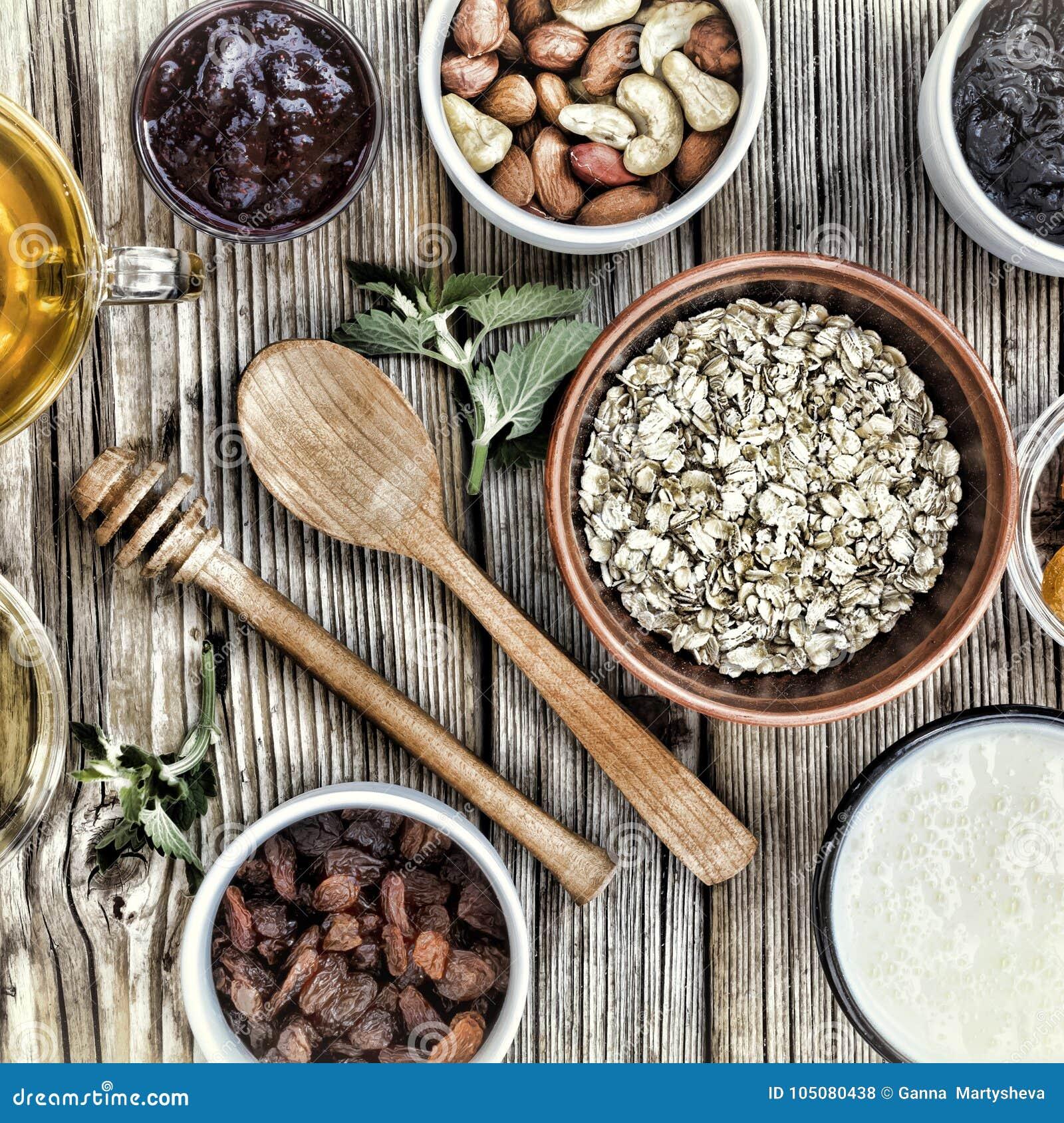 Ingredientes saudáveis do café da manhã para o muesli ou o granola em umas bacias multi-coloridas Vista superior
