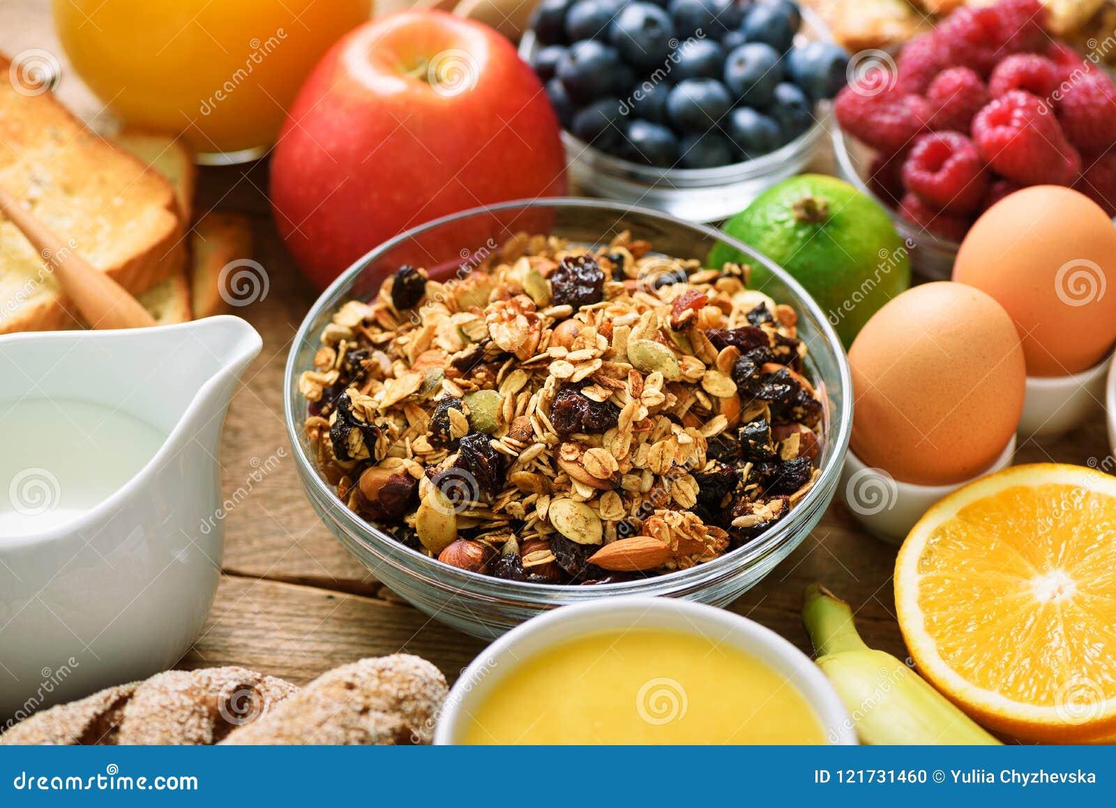 Ingredientes saudáveis do café da manhã, quadro do alimento Granola, ovo, porcas, frutos, bagas, brinde, leite, iogurte, suco de