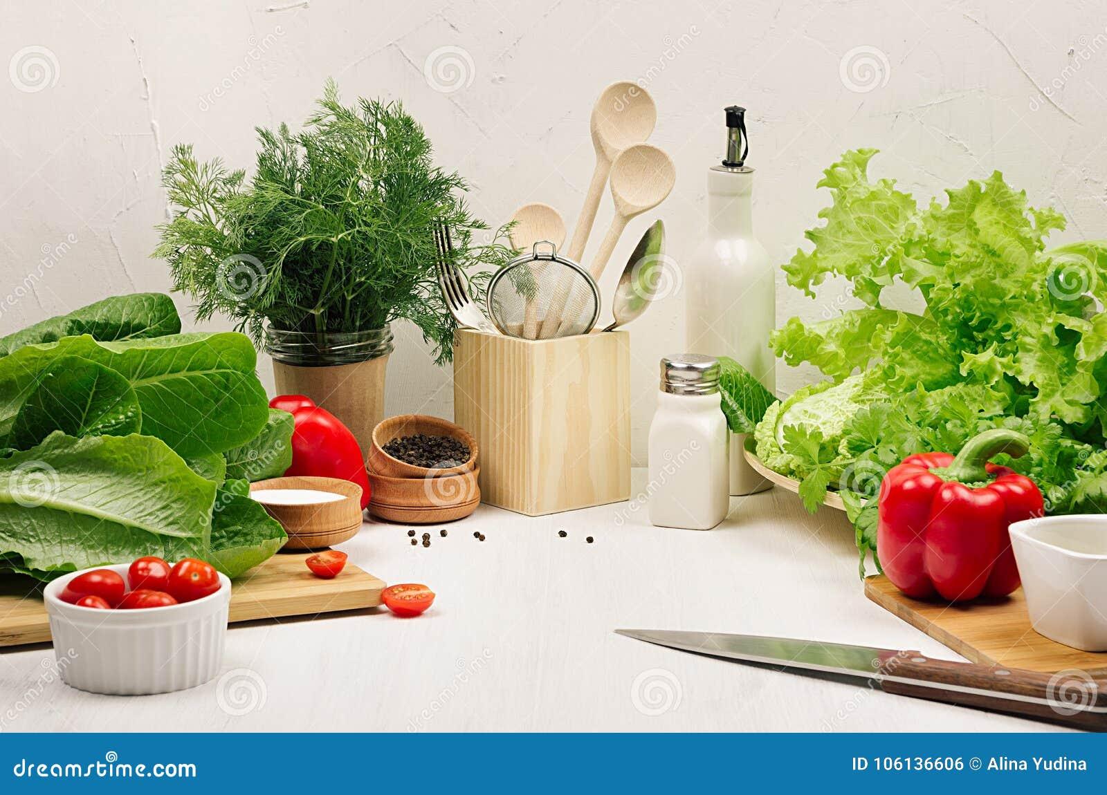 Ingredientes saudáveis do vegetariano para a salada verde e o kitchenware frescos da mola no interior elegante branco da cozinha