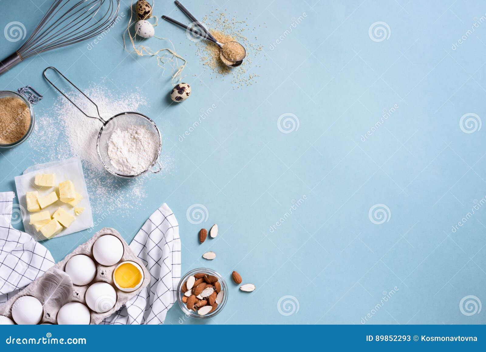 Ingredienti sani di cottura - flour, dadi della mandorla, il burro, le uova, biscotti sopra un fondo blu della tavola Pagina del
