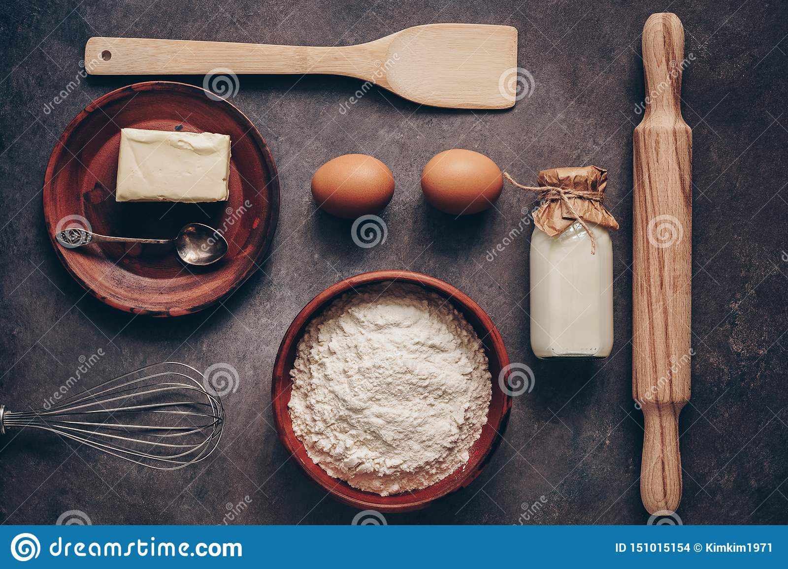 Ingredients for baking on a dark rustic background, flour, butter, eggs, rolling pin, whisk and paddle. Top view, flat lay