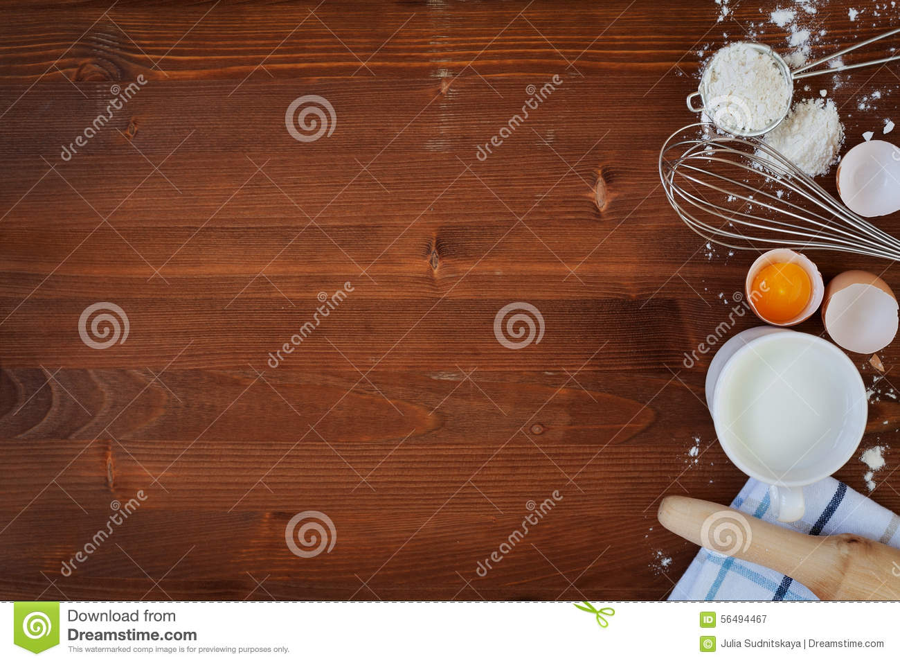 Ingredients for baking dough including flour, eggs, milk, whisk and rolling pin on wooden rustic background