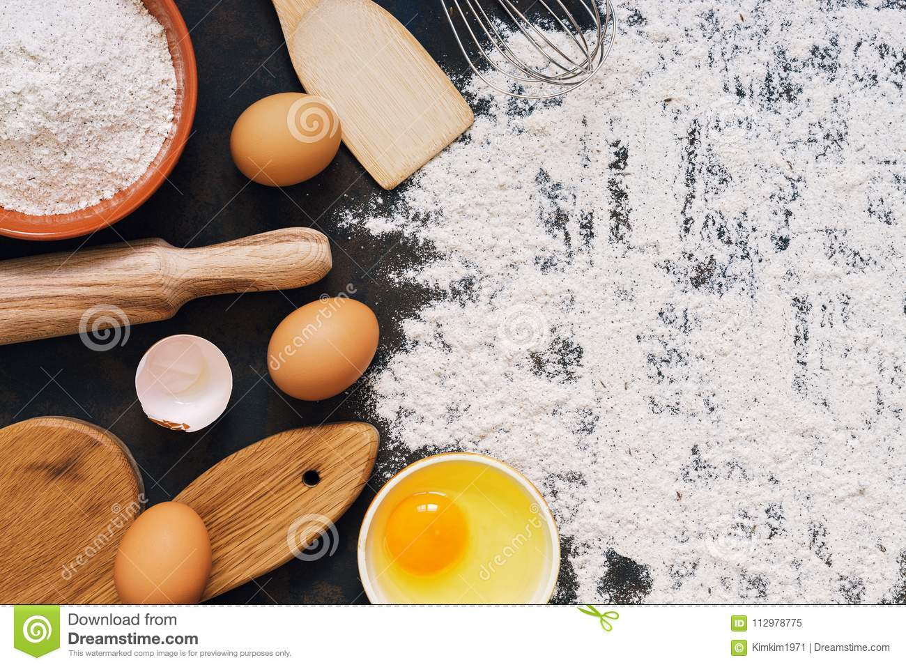 Ingredients for baking rye bread , rye flour, rolling pin, cutting board, eggs, spatula, whisk. Top view, dark rustic background,