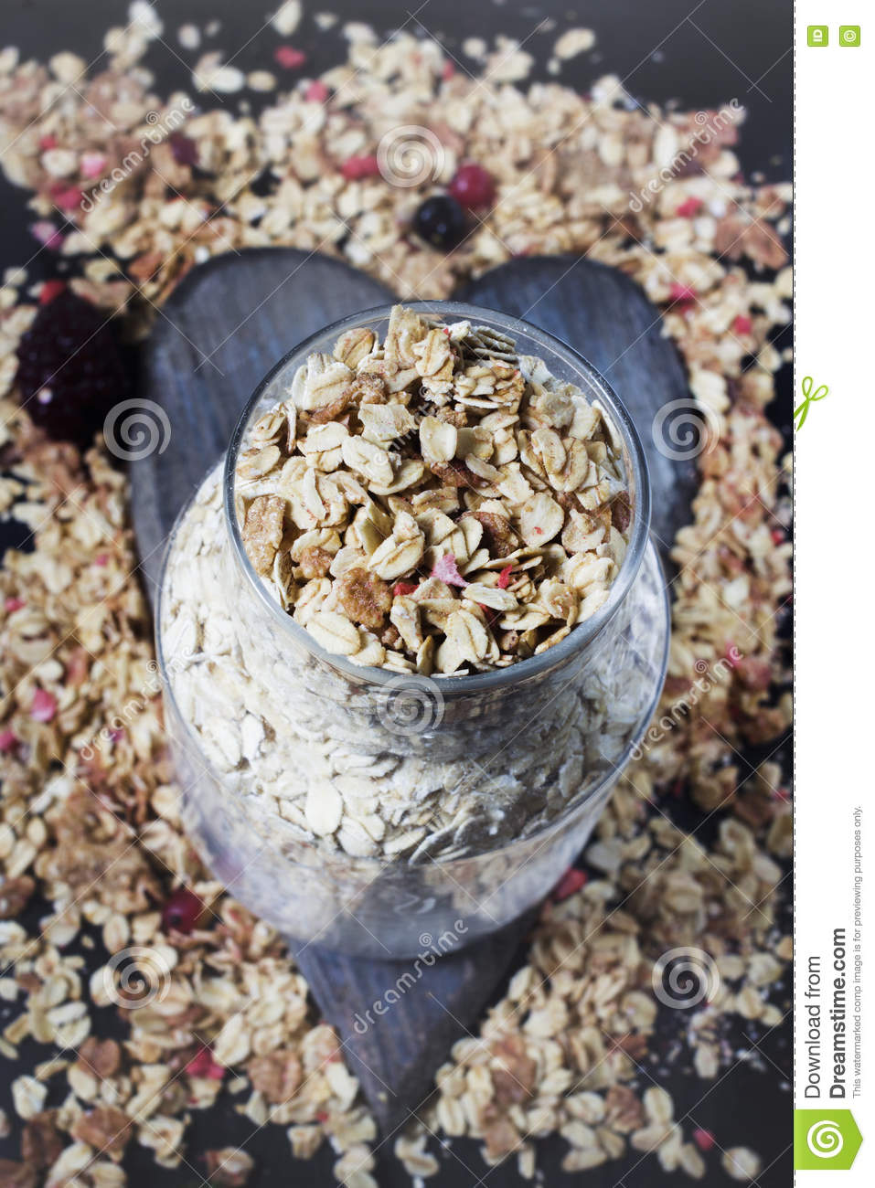 Ingredients for cooking healthy breakfast. Nuts, oat flakes, dried fruits, honey, granola, wooden heart .