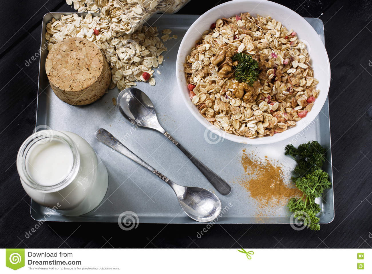 Ingredients for cooking healthy breakfast. Nuts, oat flakes, dried fruits, honey, granola, wooden heart in a white bowl.