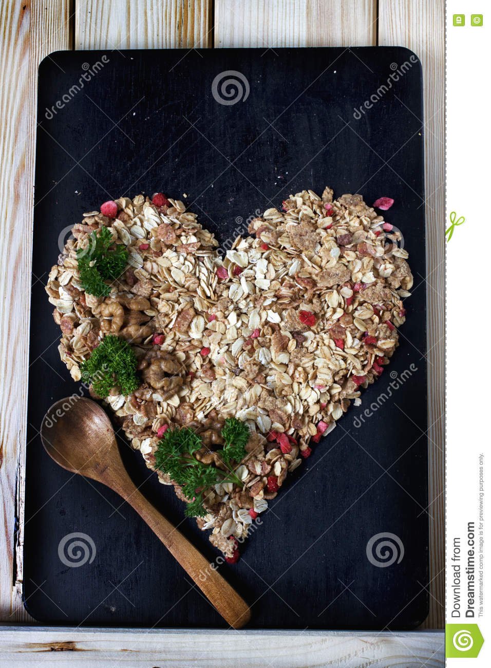 Ingredients for cooking healthy breakfast in a shape of heart. Nuts, oat flakes, dried fruits, honey, granola.