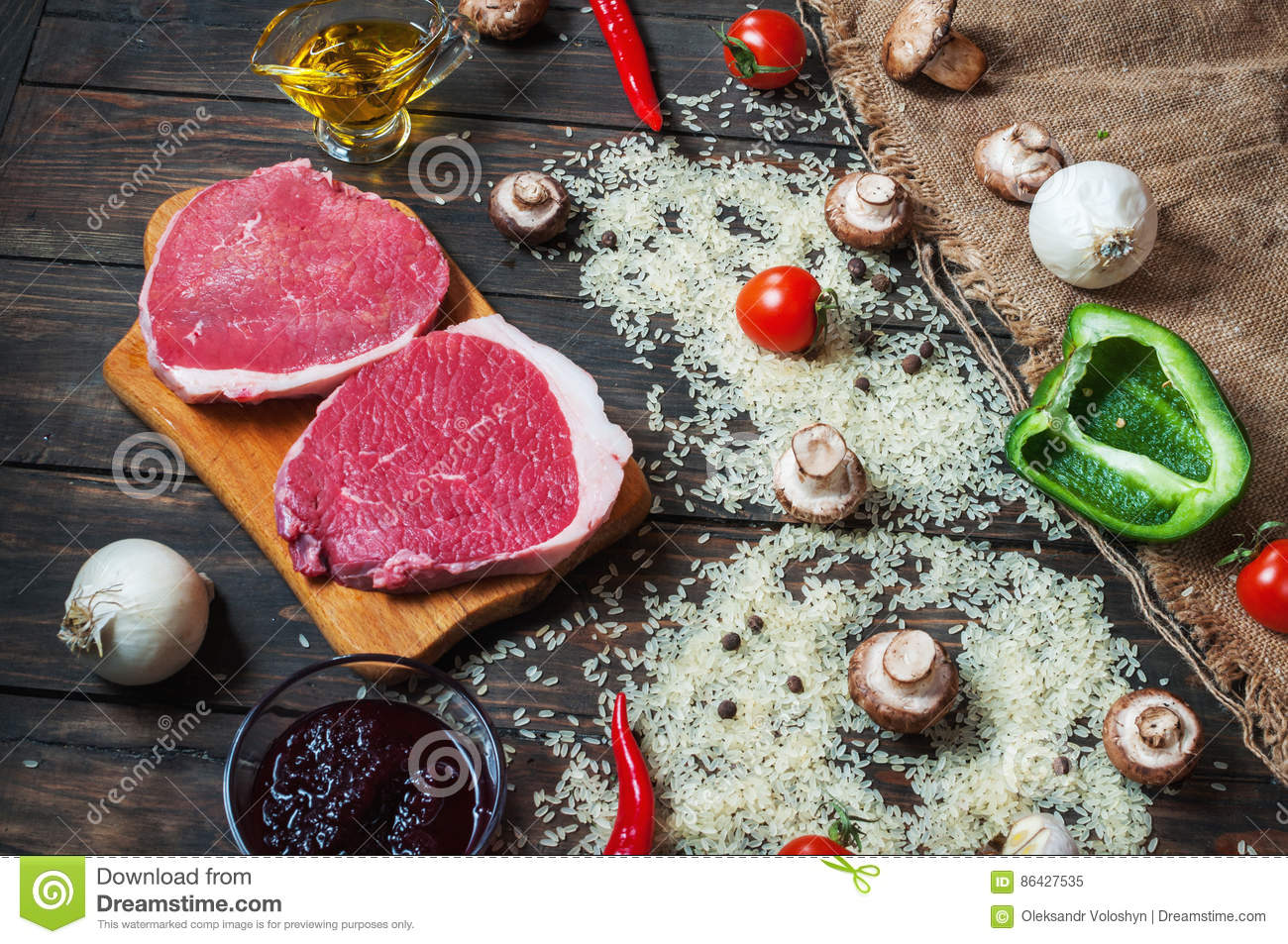 Ingredients for cooking healthy meat dinner. Raw uncooked beef rib eye steaks with mushrooms, rice, herbs and spices on table back