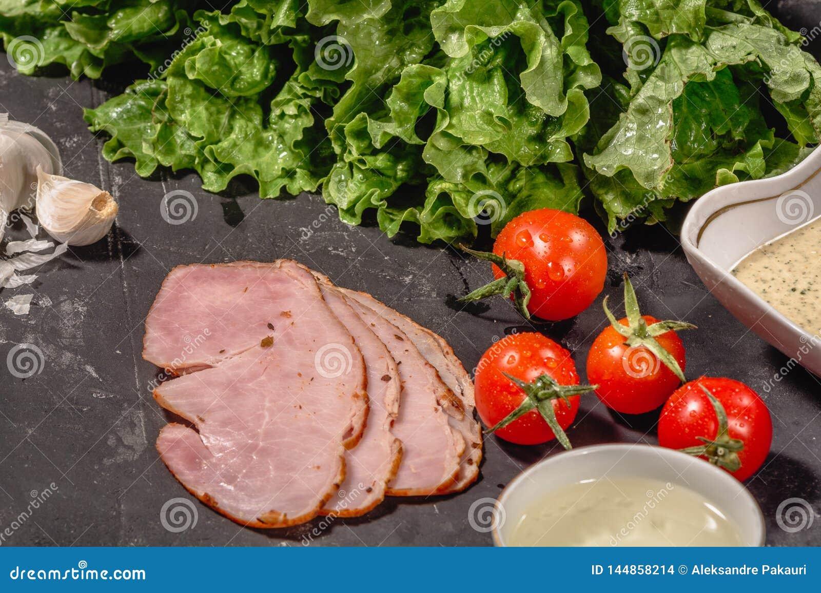 Ingredients for cooking Italian bruschetta on dark table. Italian bruschetta with cherry tomatoes, cheese sauce, salad leaves,
