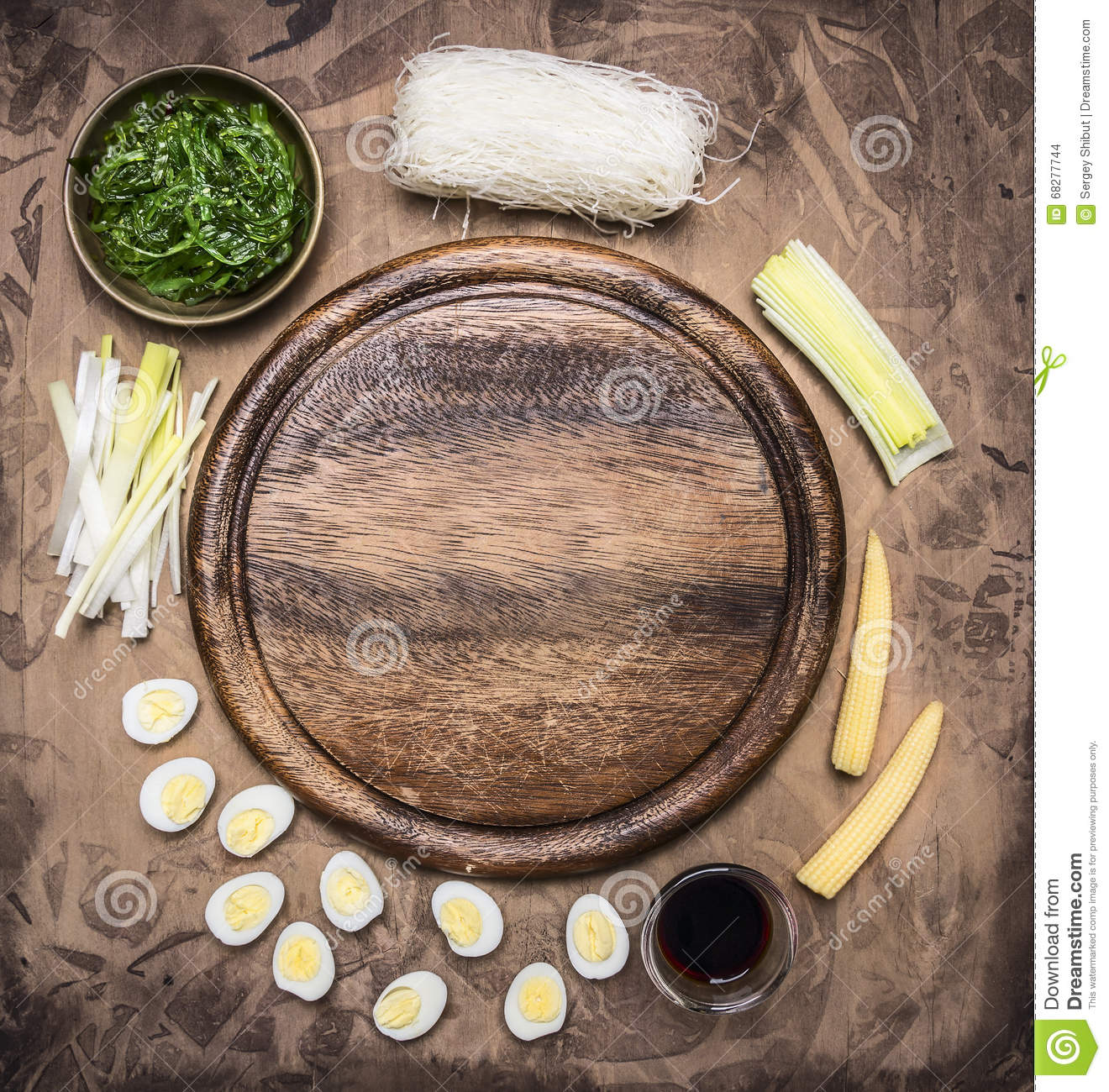 Ingredients for cooking Korean food glass noodles, chuka seaweed, boiled quail eggs, ginger, corn laid out around cutting board
