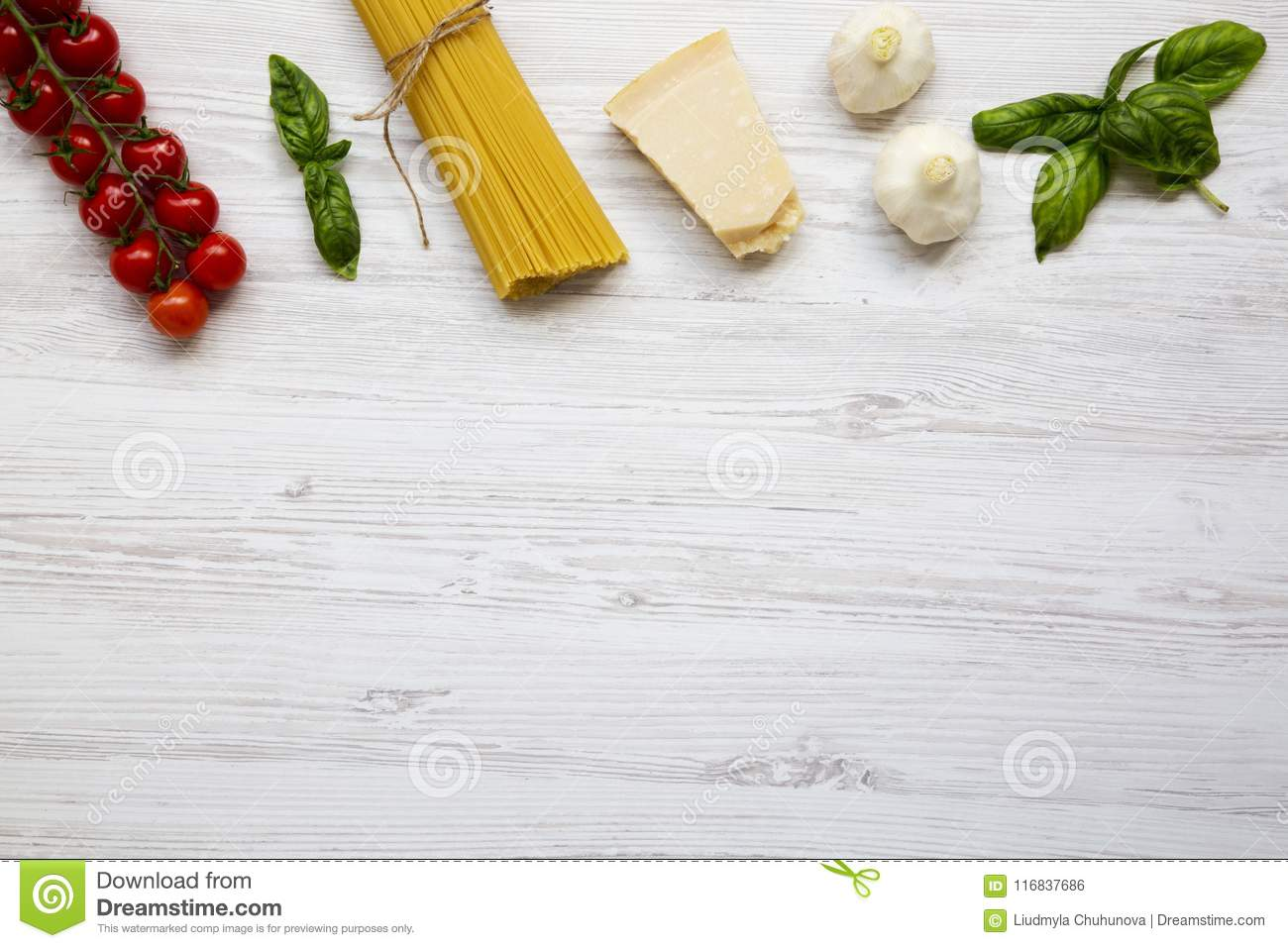 Ingredients for cooking pasta on a white wooden background.