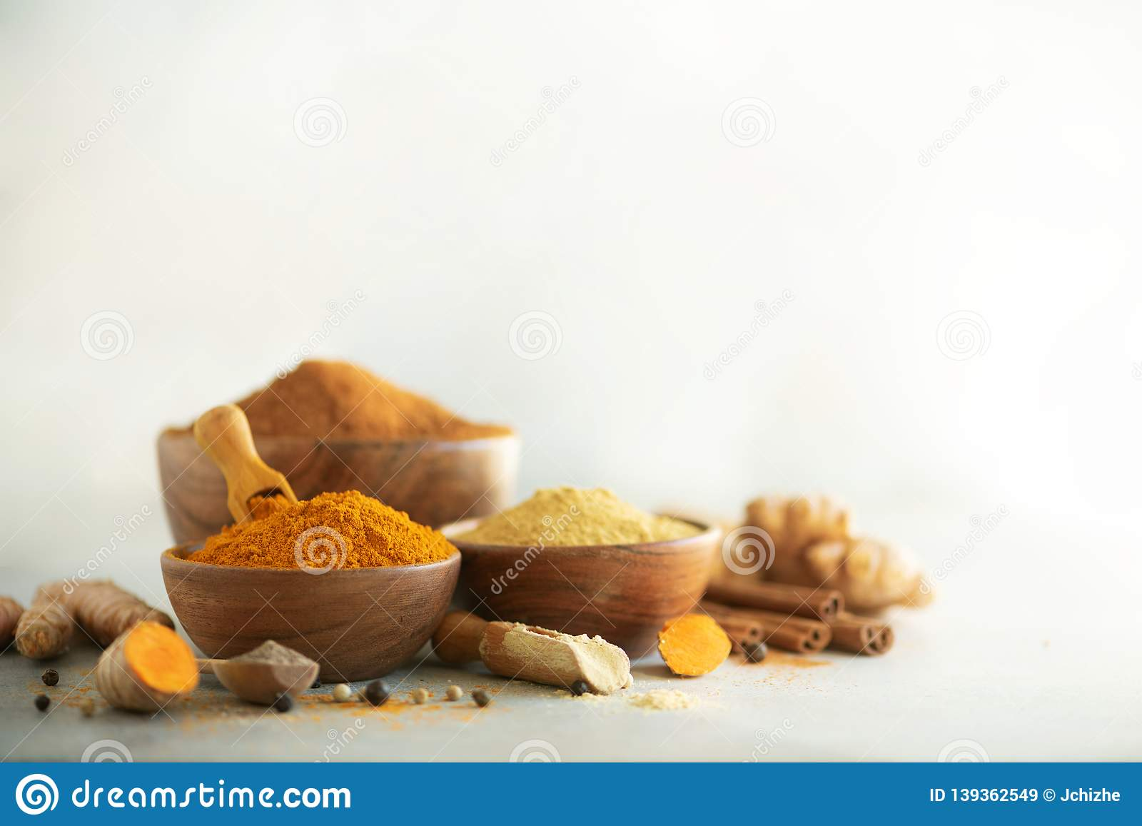 Ingredients for hot ayurvedic drink. Turmeric powder, curcuma root, cinnamon, ginger, lemon over grey background. Copy