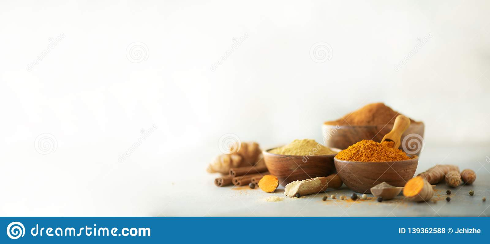 Ingredients for hot ayurvedic drink. Turmeric powder, curcuma root, cinnamon, ginger, lemon over grey background. Copy space,