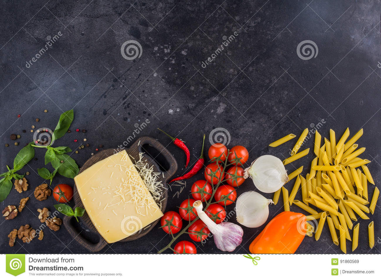 Ingredients for Italian dish. Parmesan cheese, pasta and fresh vegetables. On an old wooden background.