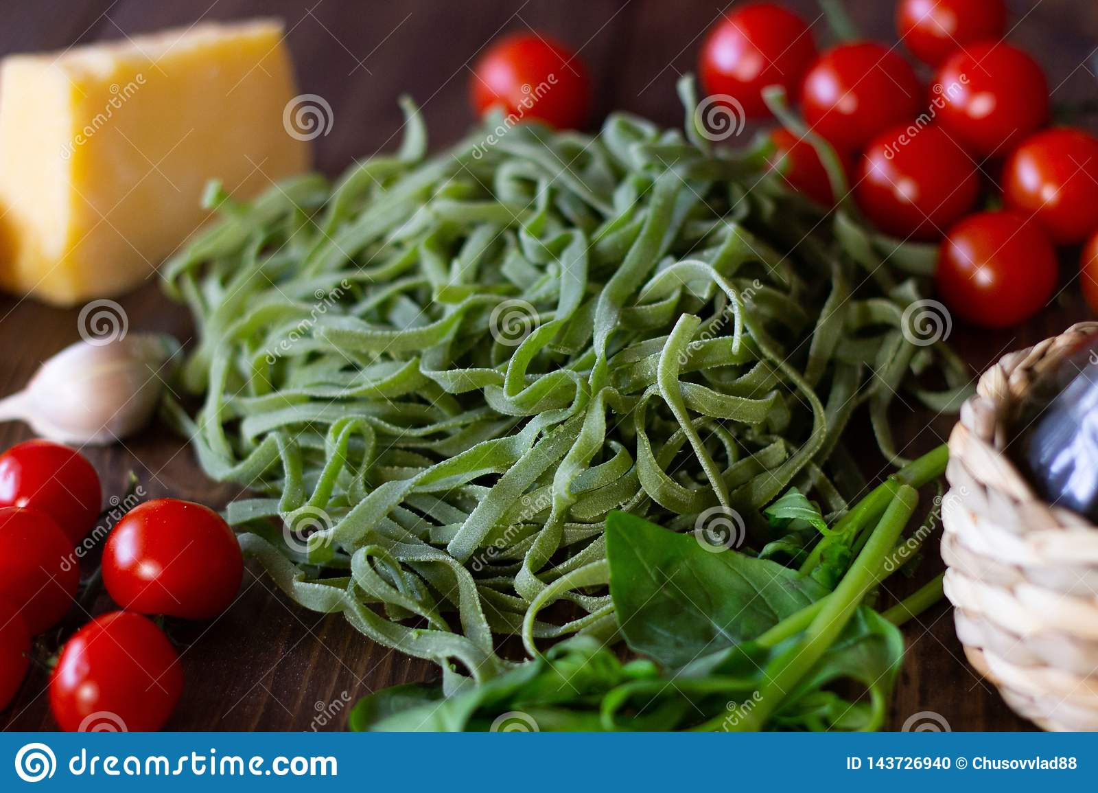 Ingredients for Italian green pasta. Wooden background