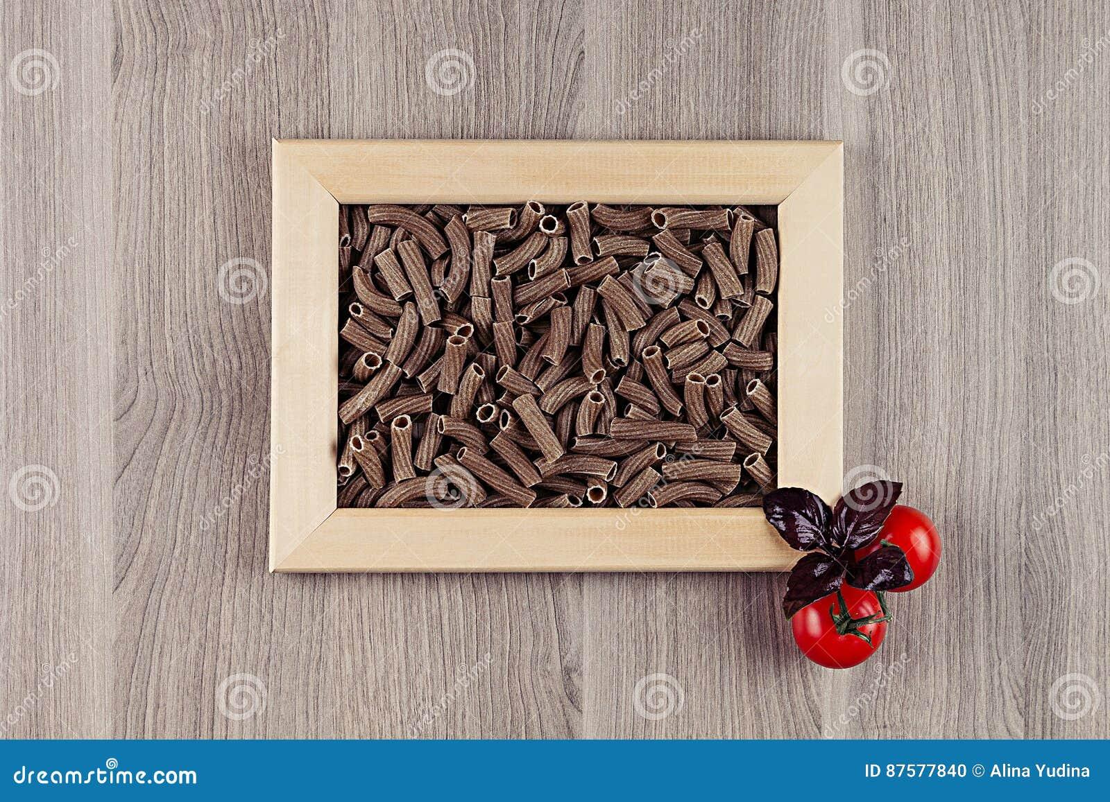 ingredients italian pasta in wood frame on beige wooden board as