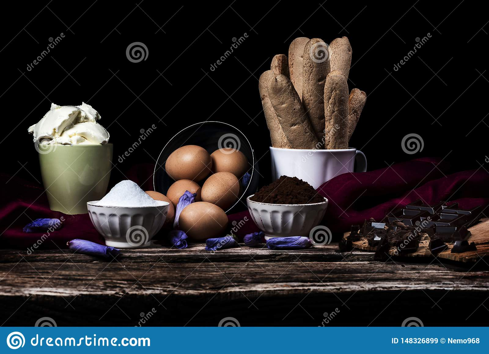Ingredients for Italian tiramisu, chocolate, coffee and mascarpone on a black background