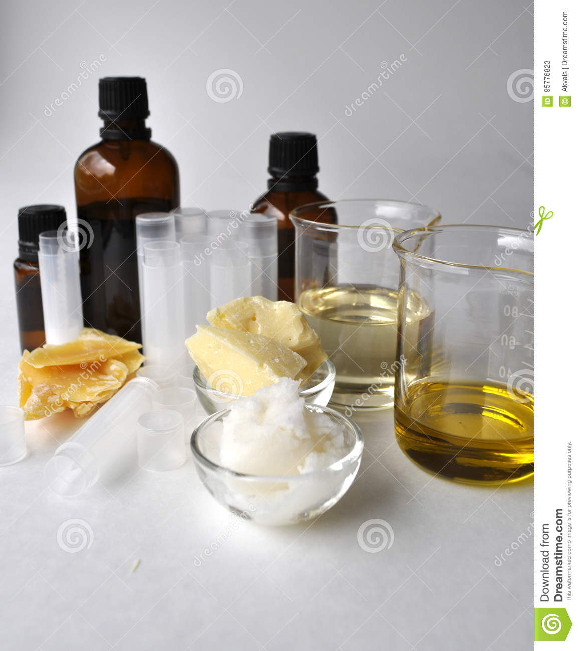 Ingredients for making natural cosmetics cacao butter, coconut, almond, jojoba and essential oils with tubes and bottles