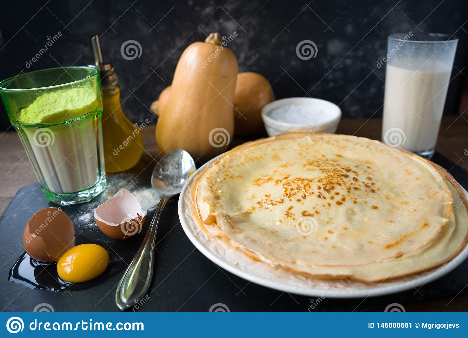 Ingredients for making pancakes - egg, butter, milk, sugar and raw dough, Rustic or rural style