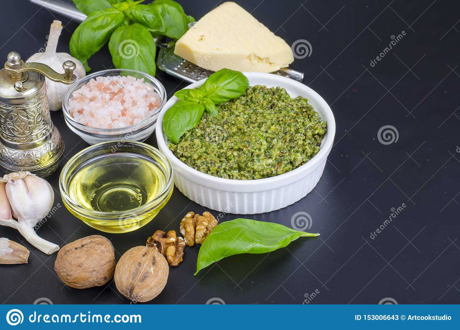 Ingredients for making pesto with walnut on black background