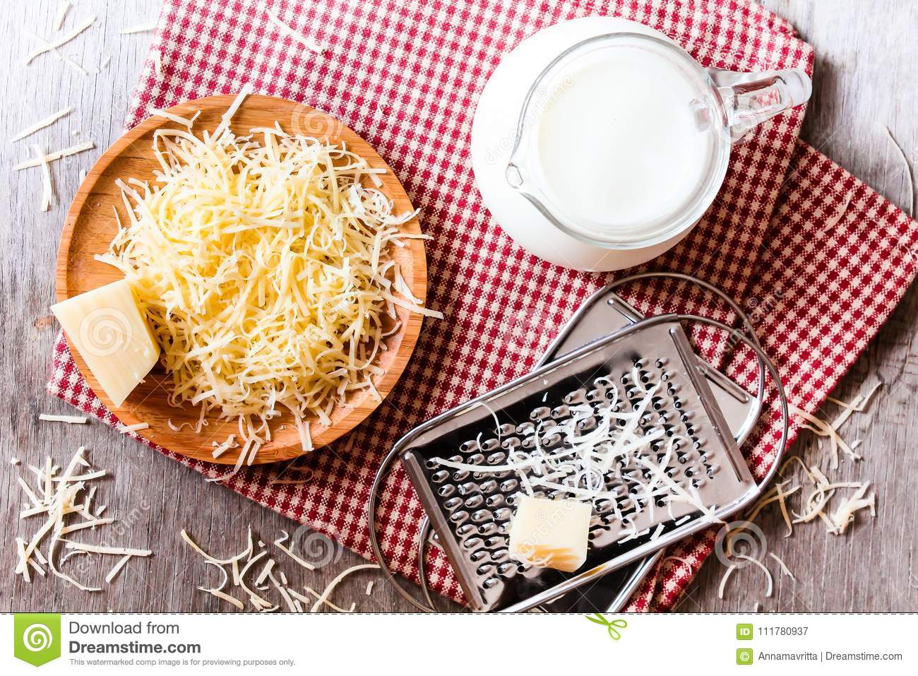 Ingredients for pasta dish or pizza - milk, freshly grated parmesan cheese on a wooden table, and kitchen utensils grater on a w
