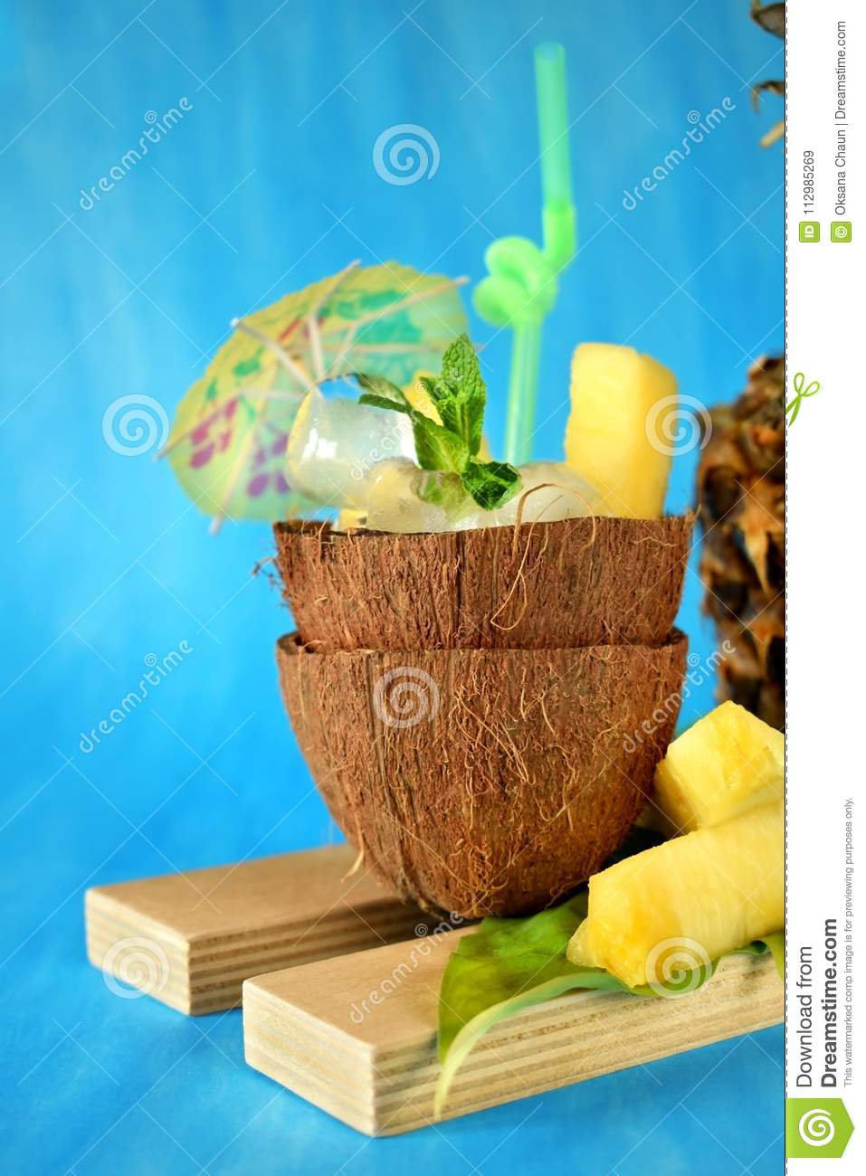 Ice cubes and pineapple pieces served in a coconut half decorated with an umbrella and straw on blue background