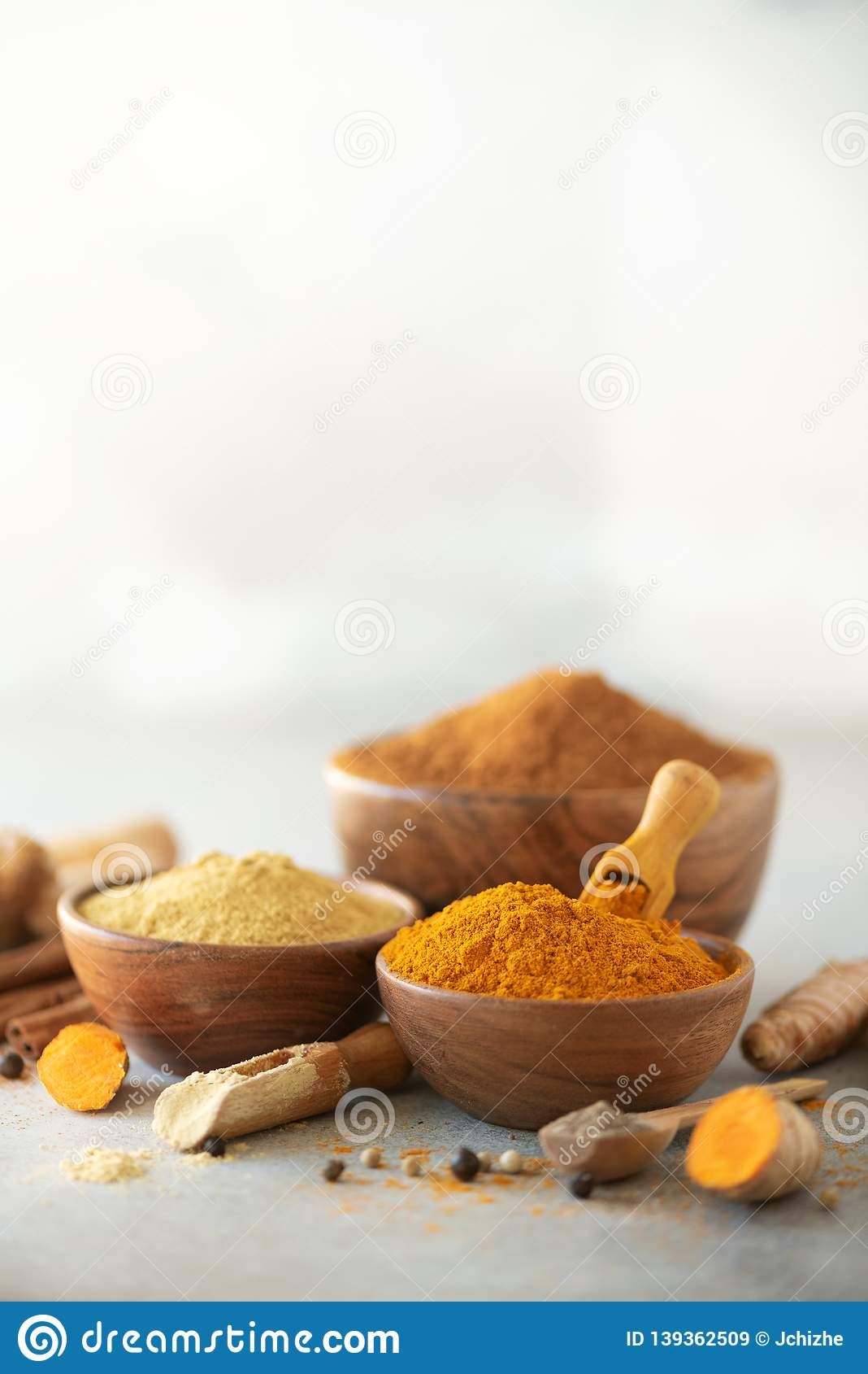 Ingredients for turmeric latte. Ground turmeric, curcuma root, cinnamon, ginger, black pepper on grey background. Spices