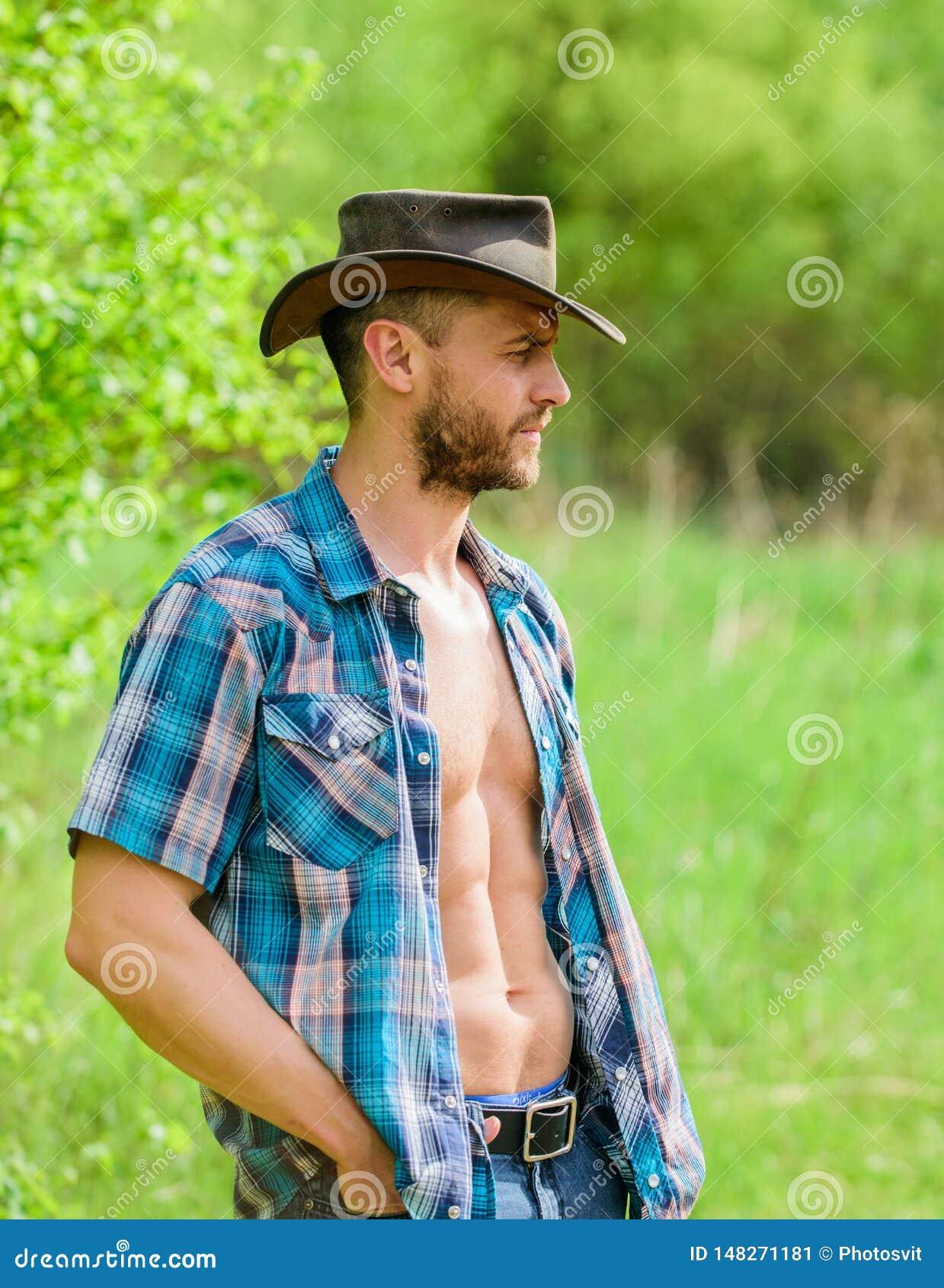 Inhaber der Ranch Torsocowboy des unrasierten Gesichtes des Mannes muskulöser Ohr des Weizens mit Schatten auf altem h?lzernem Hi