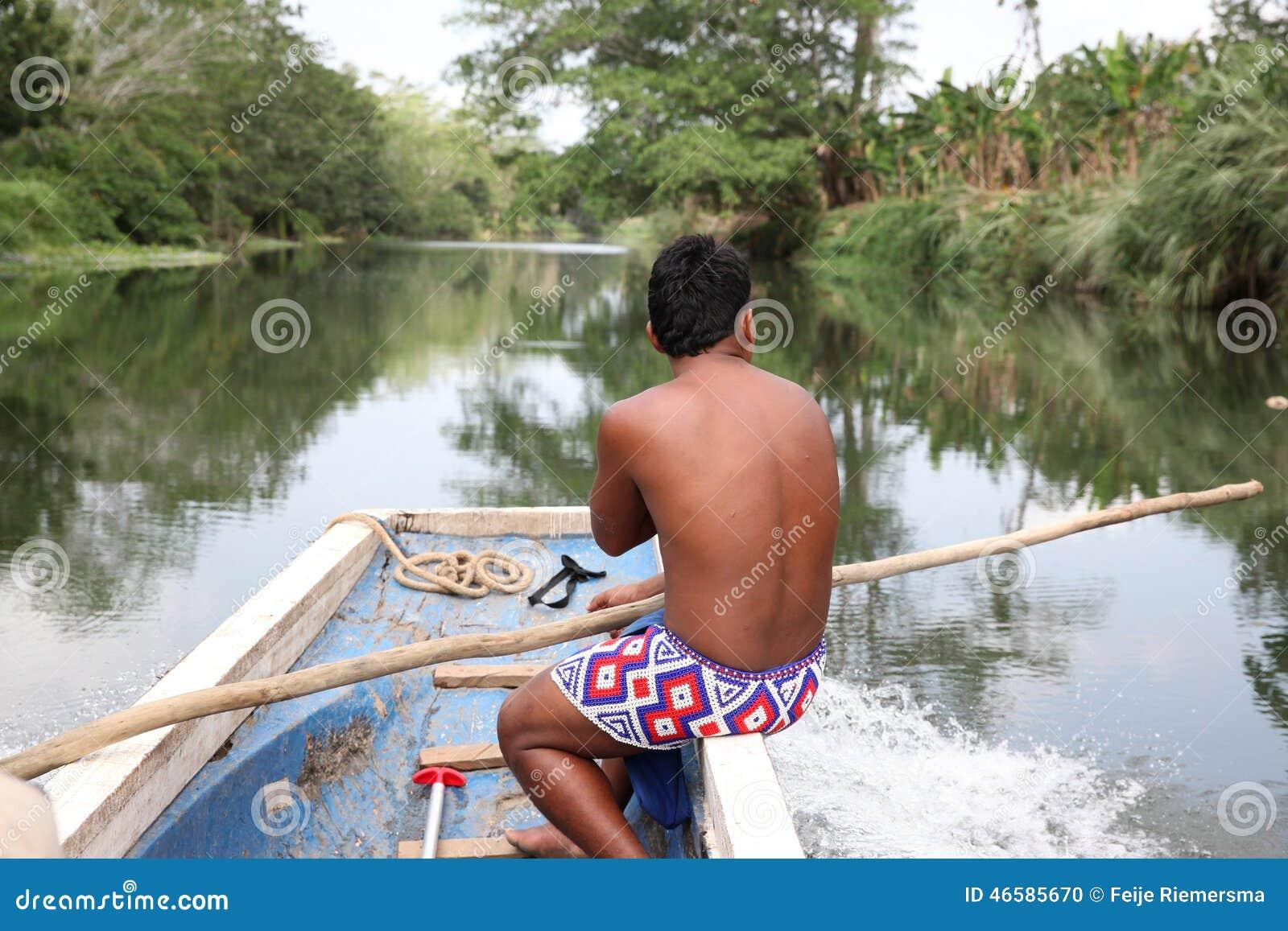 Inheemse Amerikaanse (Indische) mens op een boot op een rivier Indische mens