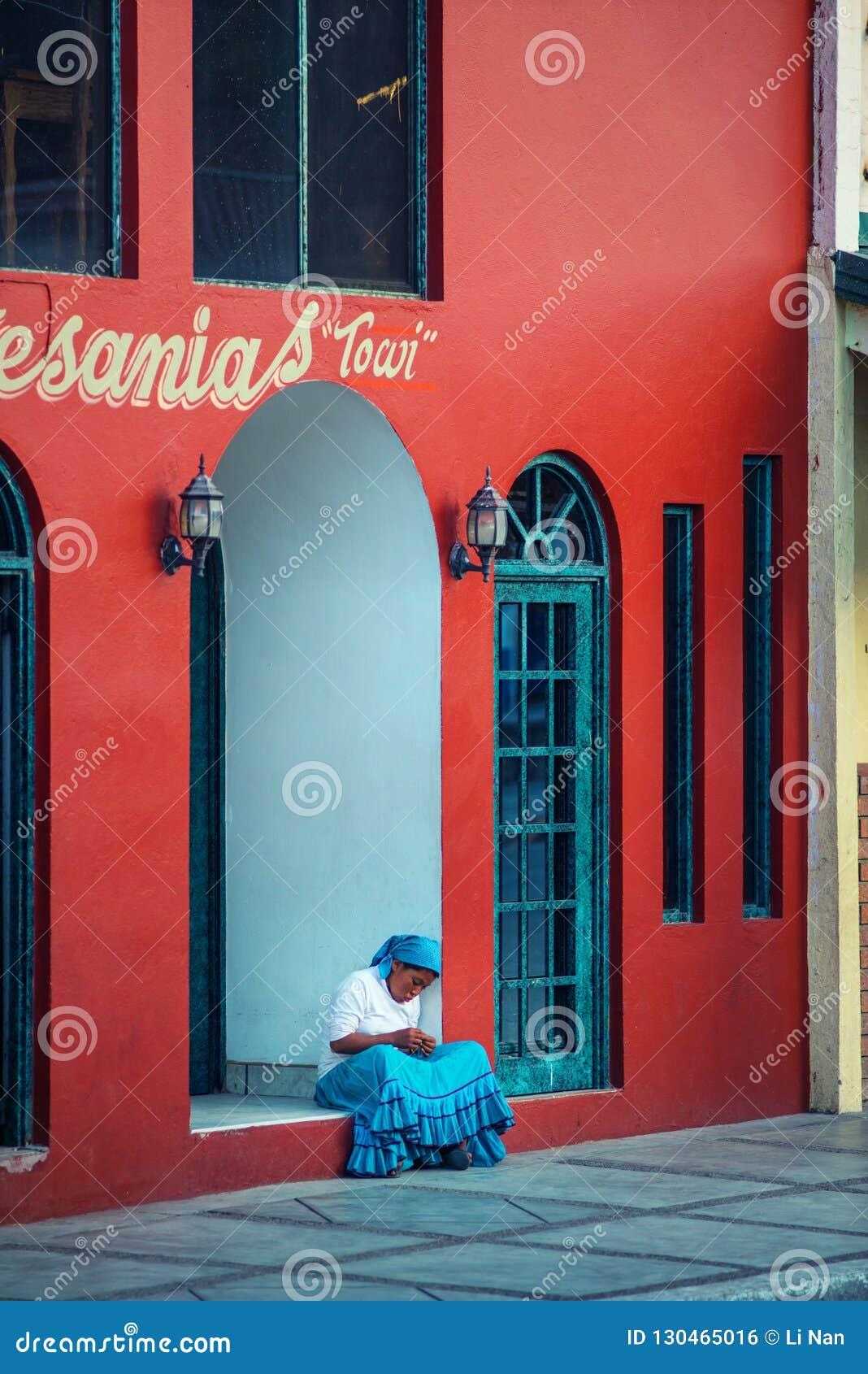 Inheemse eenzame Inheemse dame in traditionele kleurrijke kleding met een mooi huis, in Mexico, Amerika
