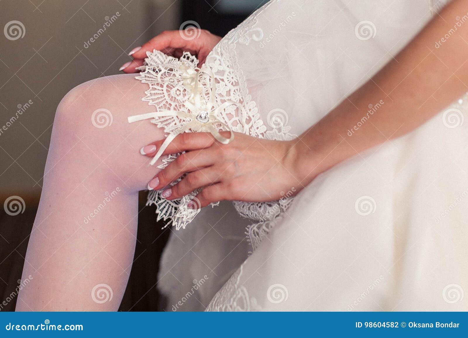 Inizio del giorno delle nozze La sposa indossa una giarrettiera di nozze