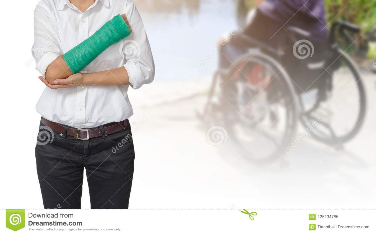 Injured woman with green cast on hand and arm on blurre