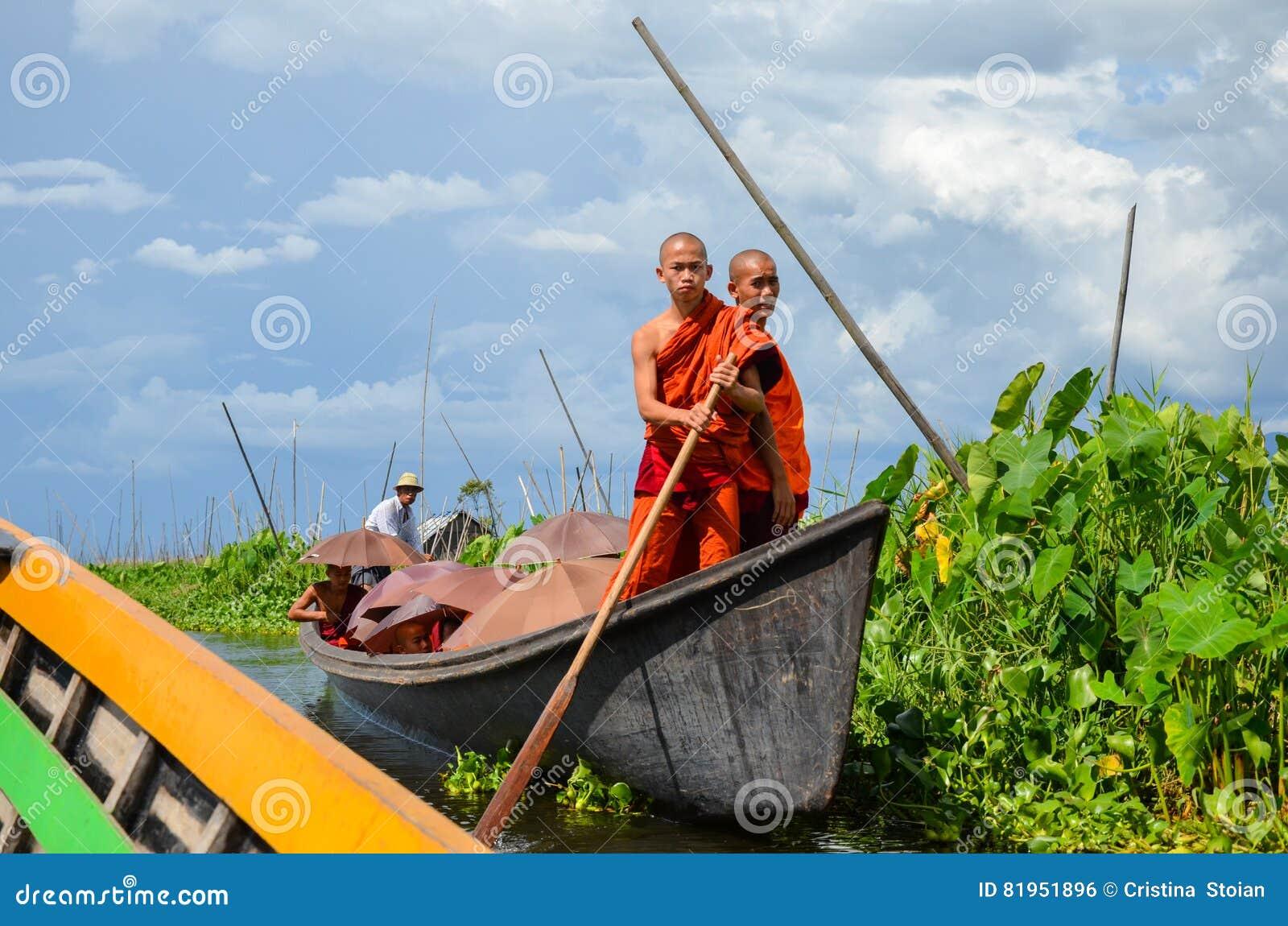 INLE-SEE, MYANMAR 26. SEPTEMBER 2016: Buddist-Mönche, die einen Lastkahn auf dem Inle See schaufeln