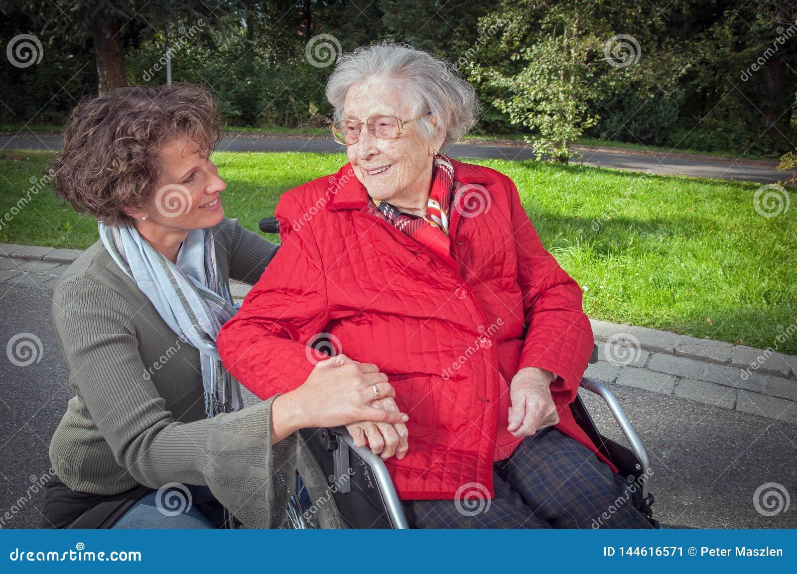 Innehavhand för ung kvinna av den gamla damen som sitter i rullstol