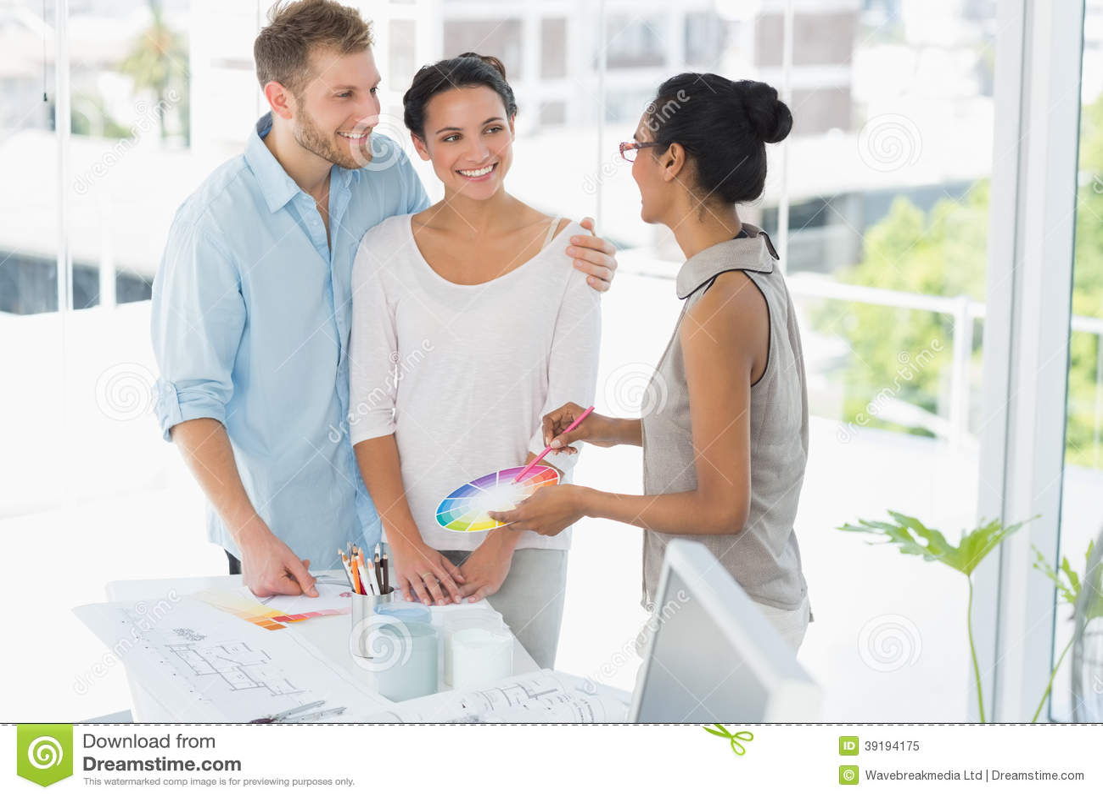Innenarchitekt, der den glücklichen jungen Kunden Farbrad zeigt