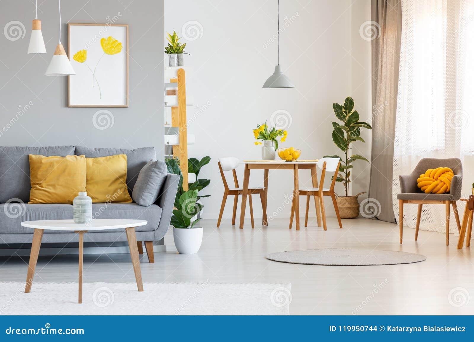 Innenraum des Lebenund Esszimmers des offenen Raumes mit grauem Sofa, woode