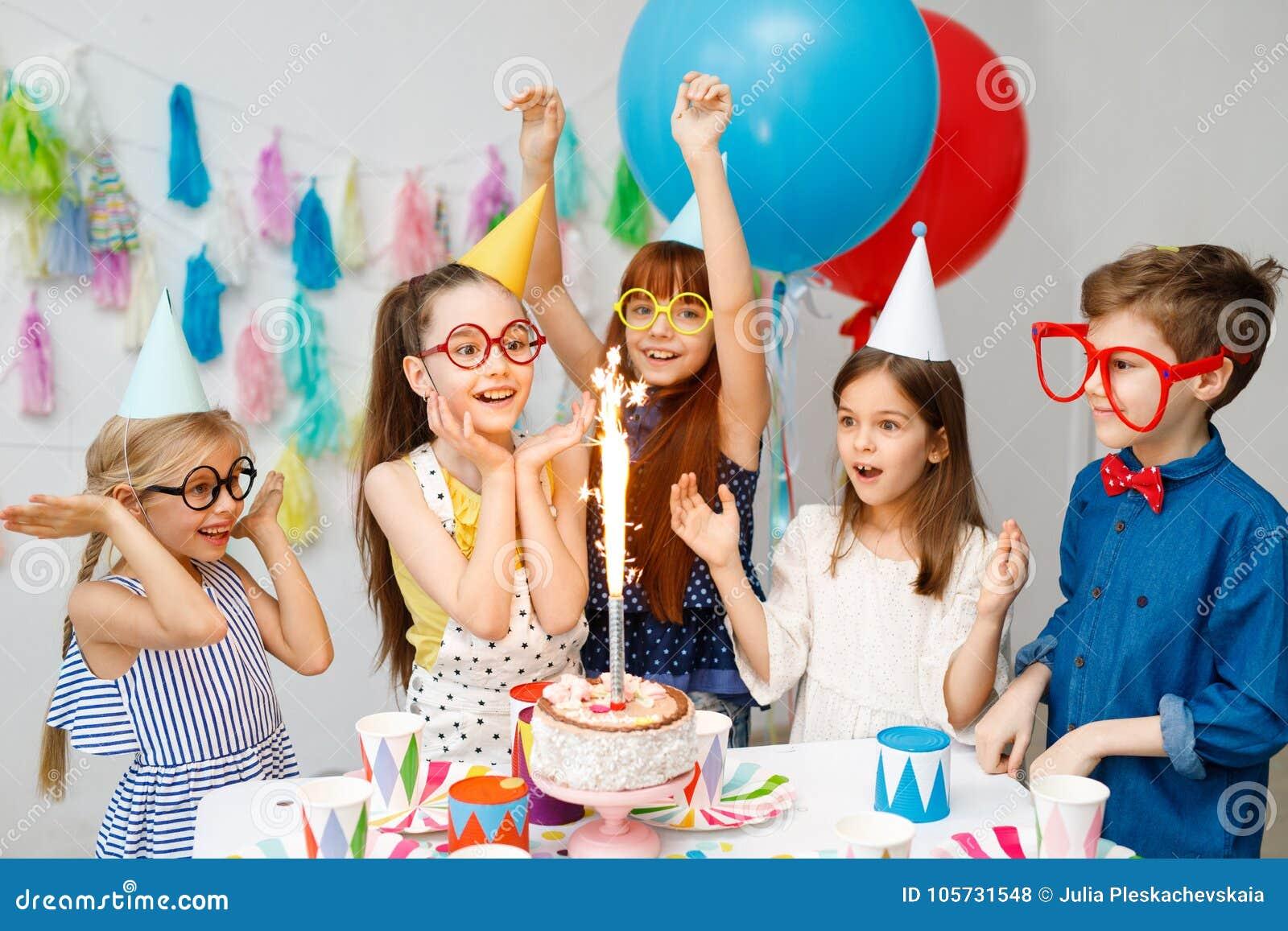 Innenschuß von glücklichen frohen Kindern betrachten großen Schein auf Kuchen, feiern Geburtstag, ungeschickte große Schauspiele