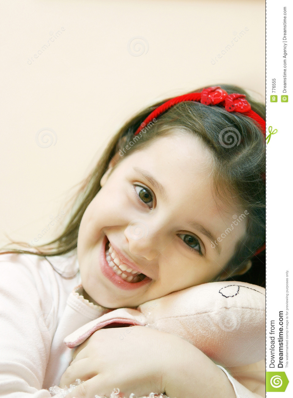 Beautiful six year old girl smiles with innocence, holding her toy