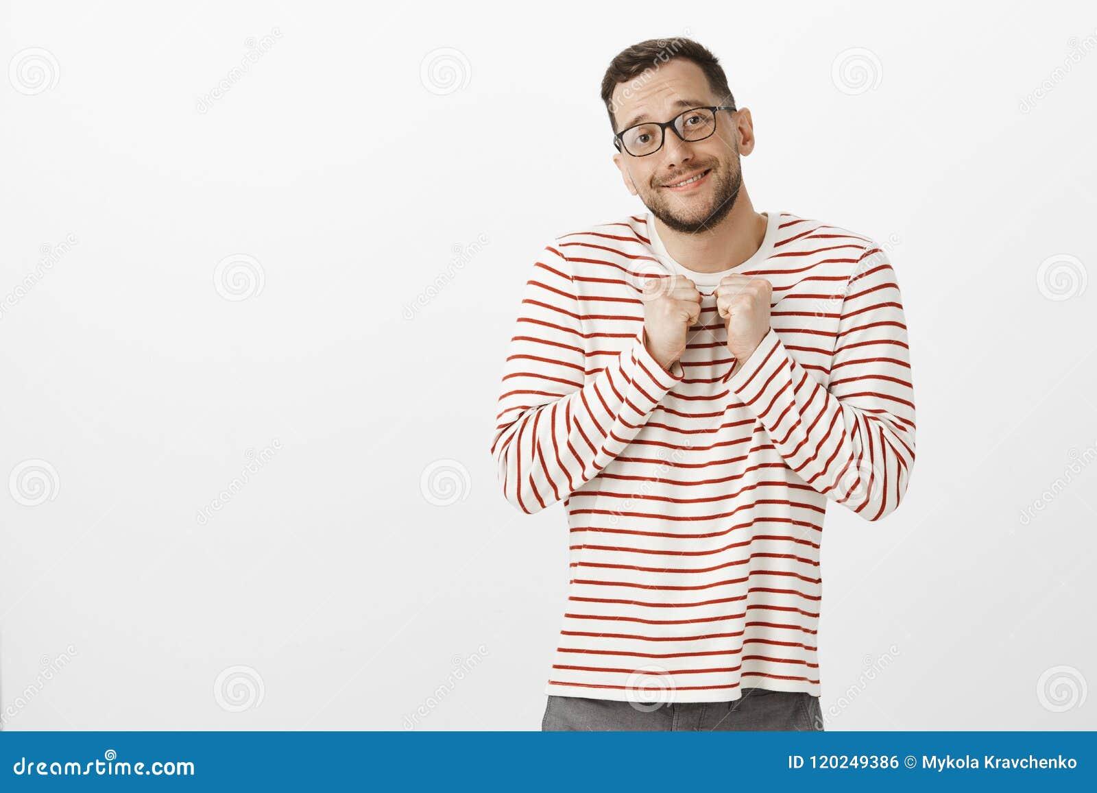 Inomhus skott av den gulliga mjuka vuxna glade mannen med borstet i svarta exponeringsglas som grinar och rymmer handen nära brös