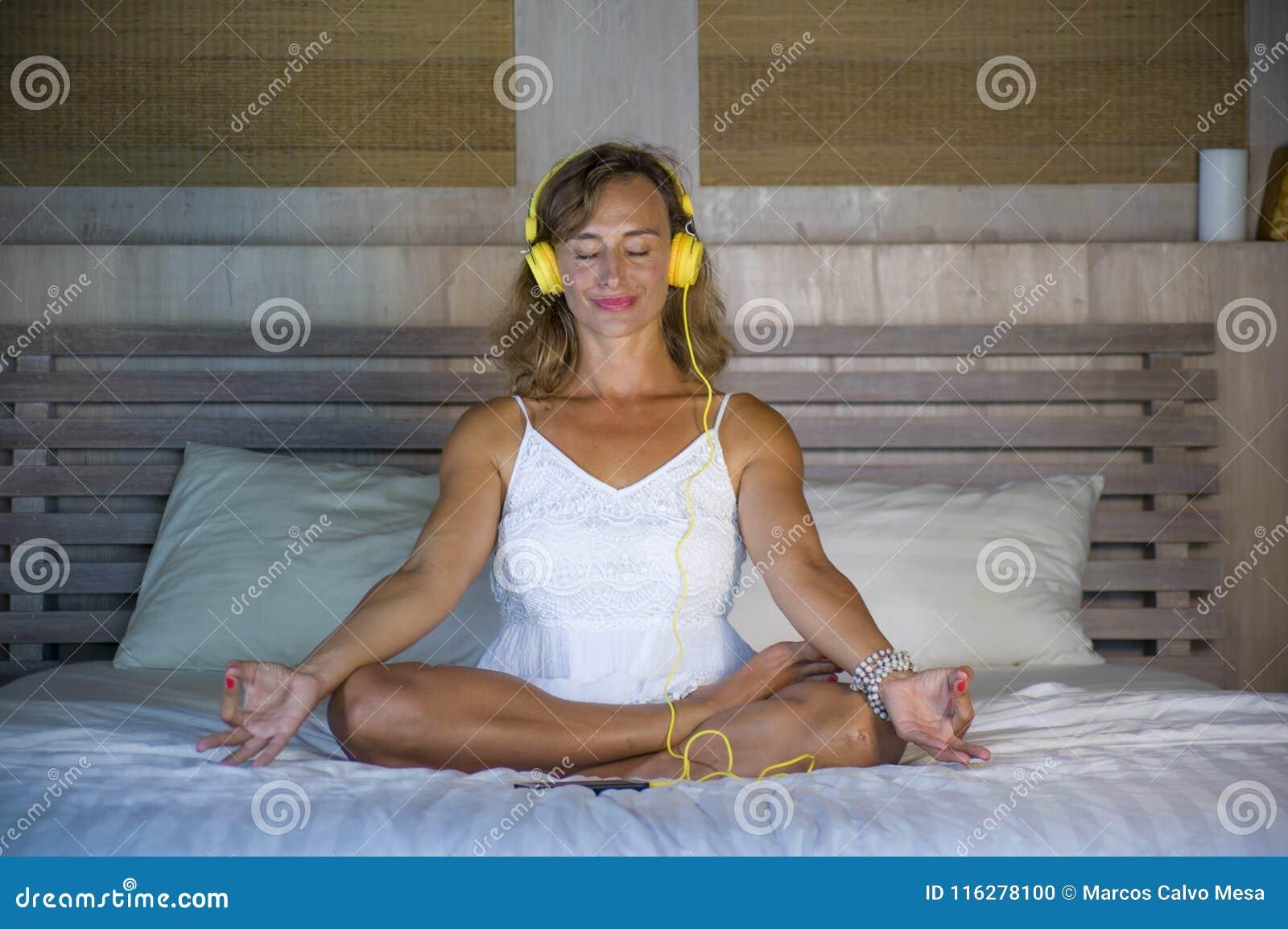 Inomhus stående av den härliga och färdiga sunda kvinna30-tal som öva yoga som lyssnar till musik med hörlurar i säng som poserar