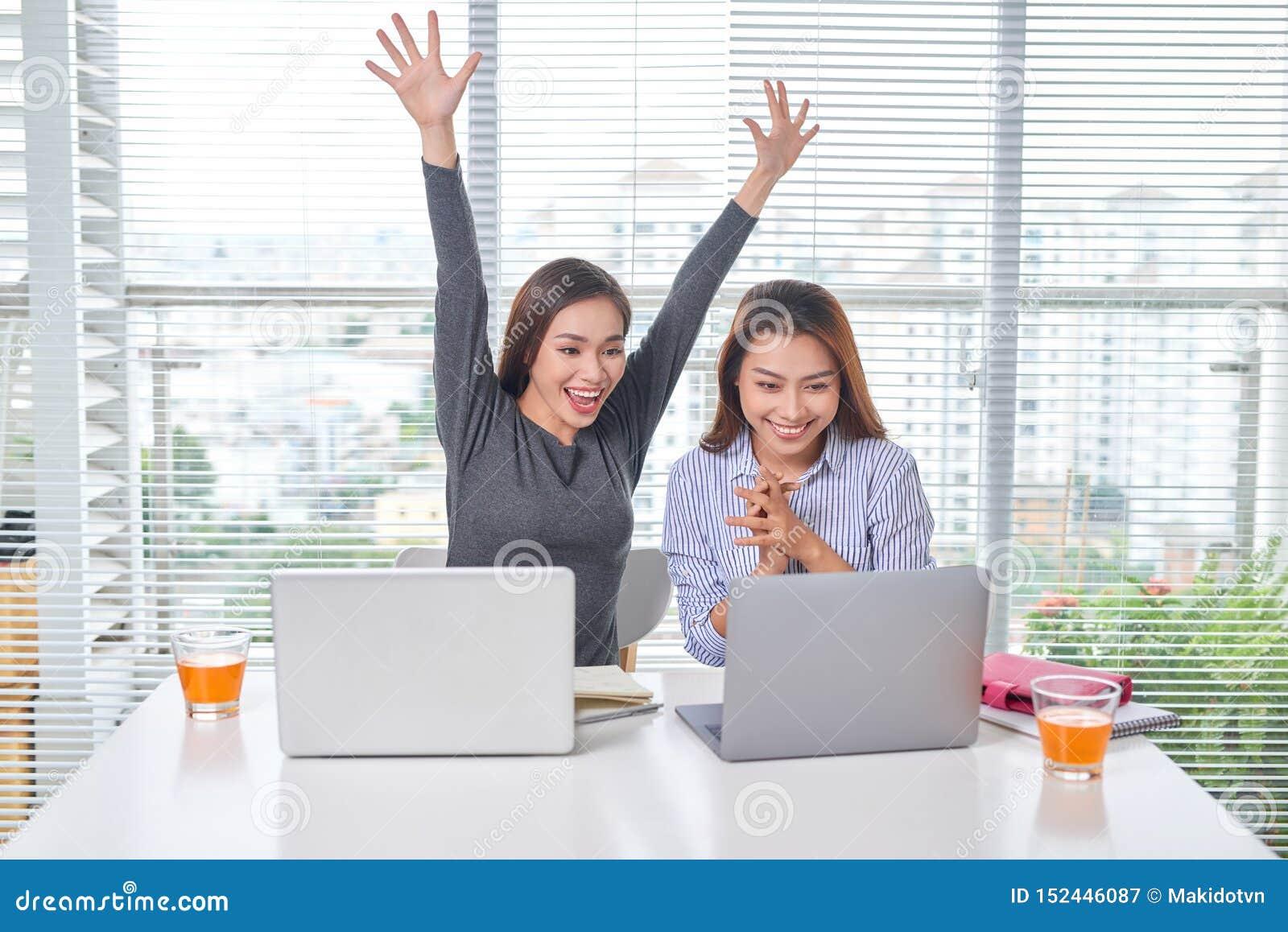 Inomhus st?ende av att le flickor som tillsammans i regeringsst?llning arbetar N?tt kvinna som spenderar tid med v?nnen under avb