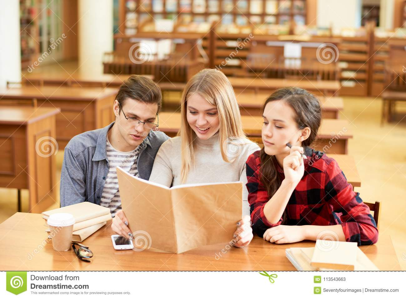 Inquisitive Students Reading Popular Science Book Stock Image