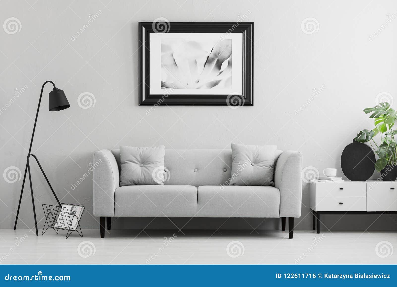 Inramat foto på en vägg ovanför ett infall, den gråa soffan med kuddar i en minimalist vardagsruminre och stället för en tabell V