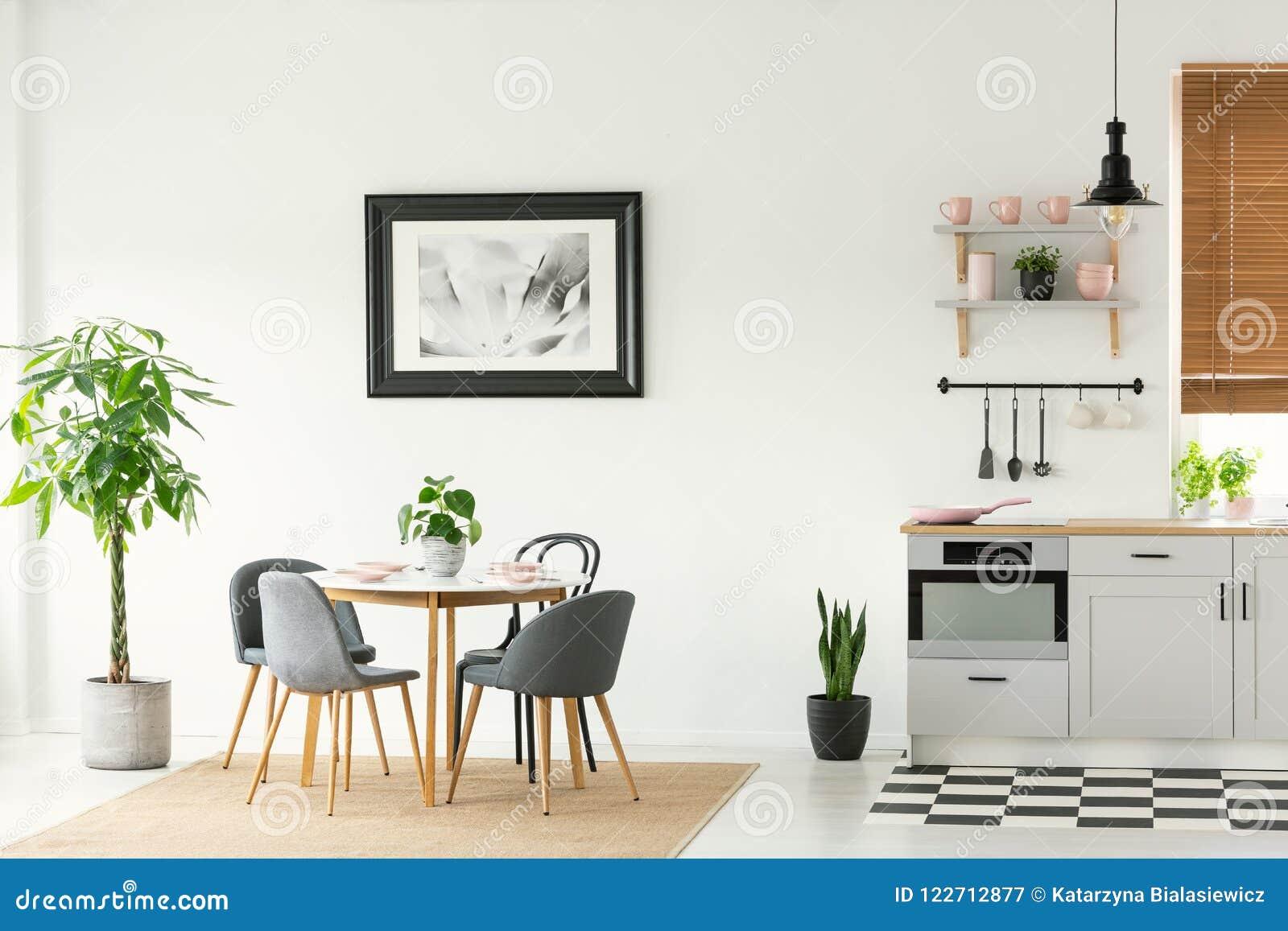 Inramat foto på en vit vägg i en öppet utrymmematsal- och kökinre med moderna trämöblemang och växter