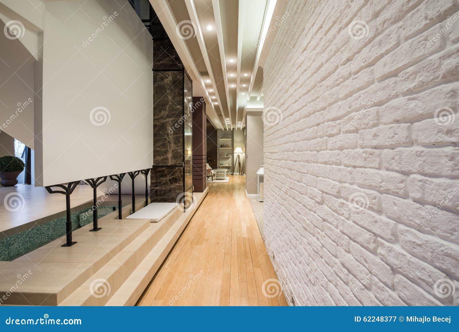 Inre av en lång korridor med den vita tegelstenväggen