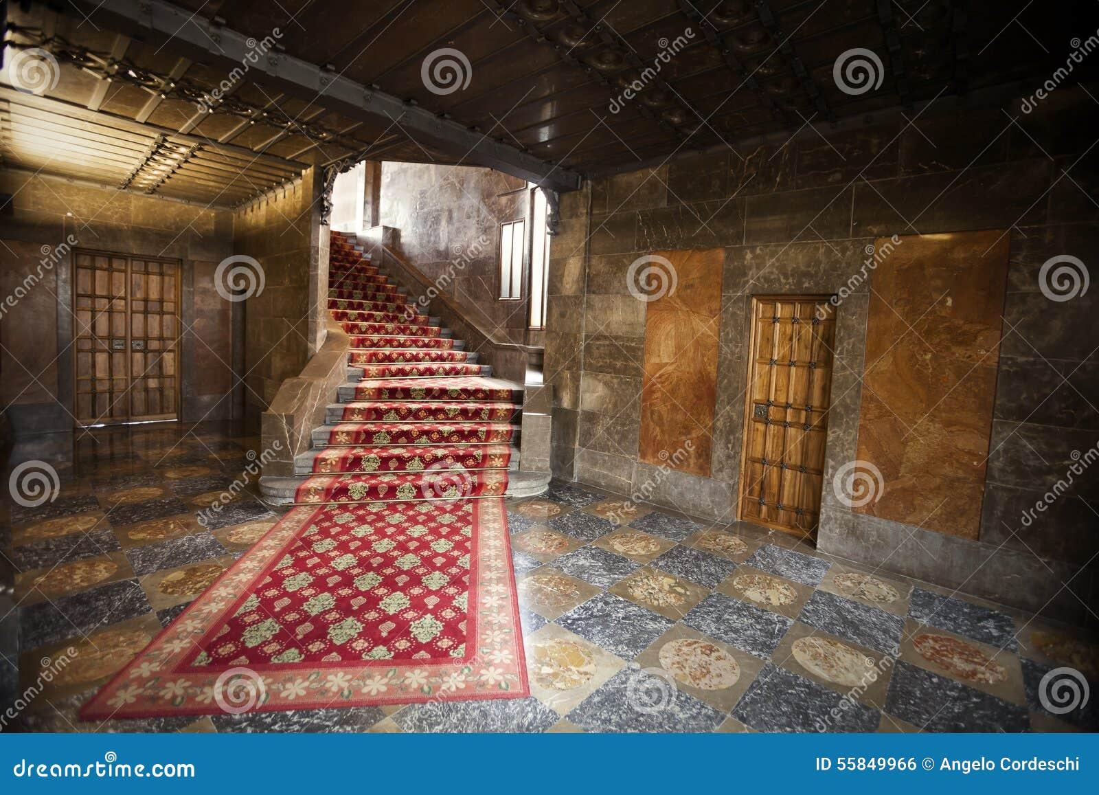 Inre av ett gammalt spanjorhus med röd matta, trappa och dörrar ...