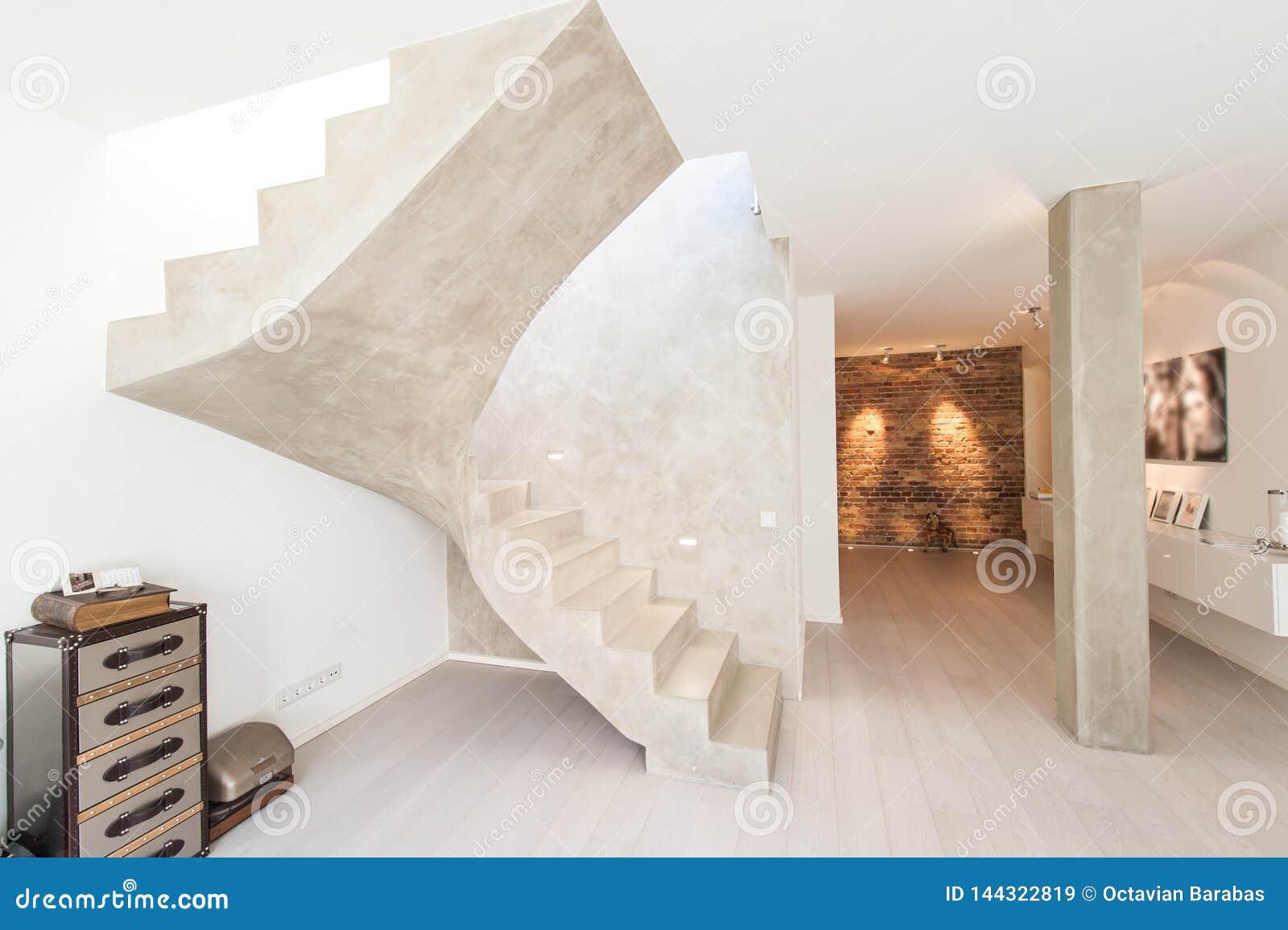 Inre av modernt rum med pelaren och trappa