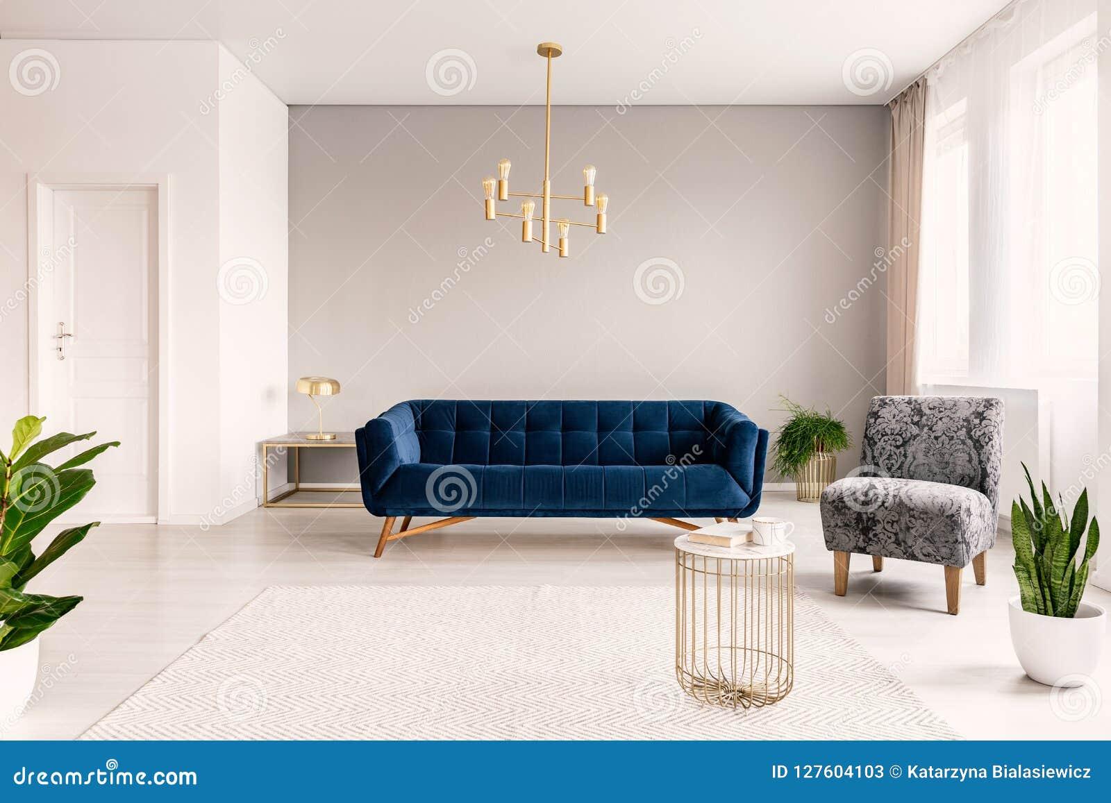 Inre för kopieringsutrymmevardagsrum med ett mörker - blå soffa, en grå fåtölj och guldbrytningar Verkligt foto