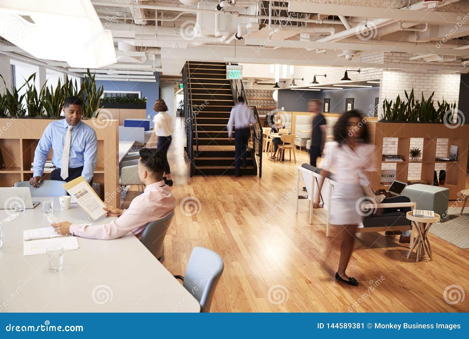 Inre sikt av det moderna öppna plankontoret med suddiga affärsmän och affärskvinnor