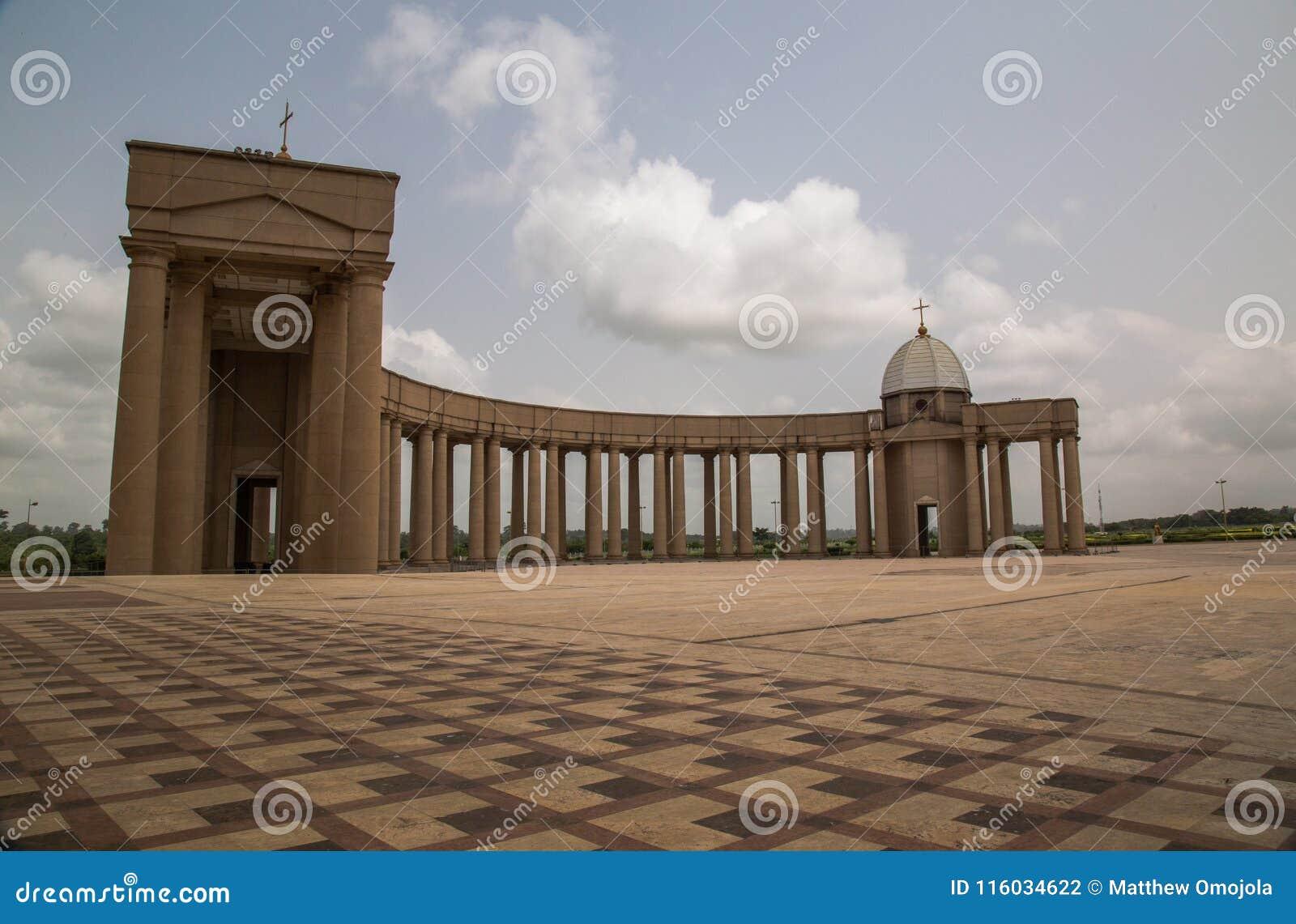 Inre sikt av en av de doric kolonnaderna av basilikan av vår dam av fred med inställningssolen till det västra